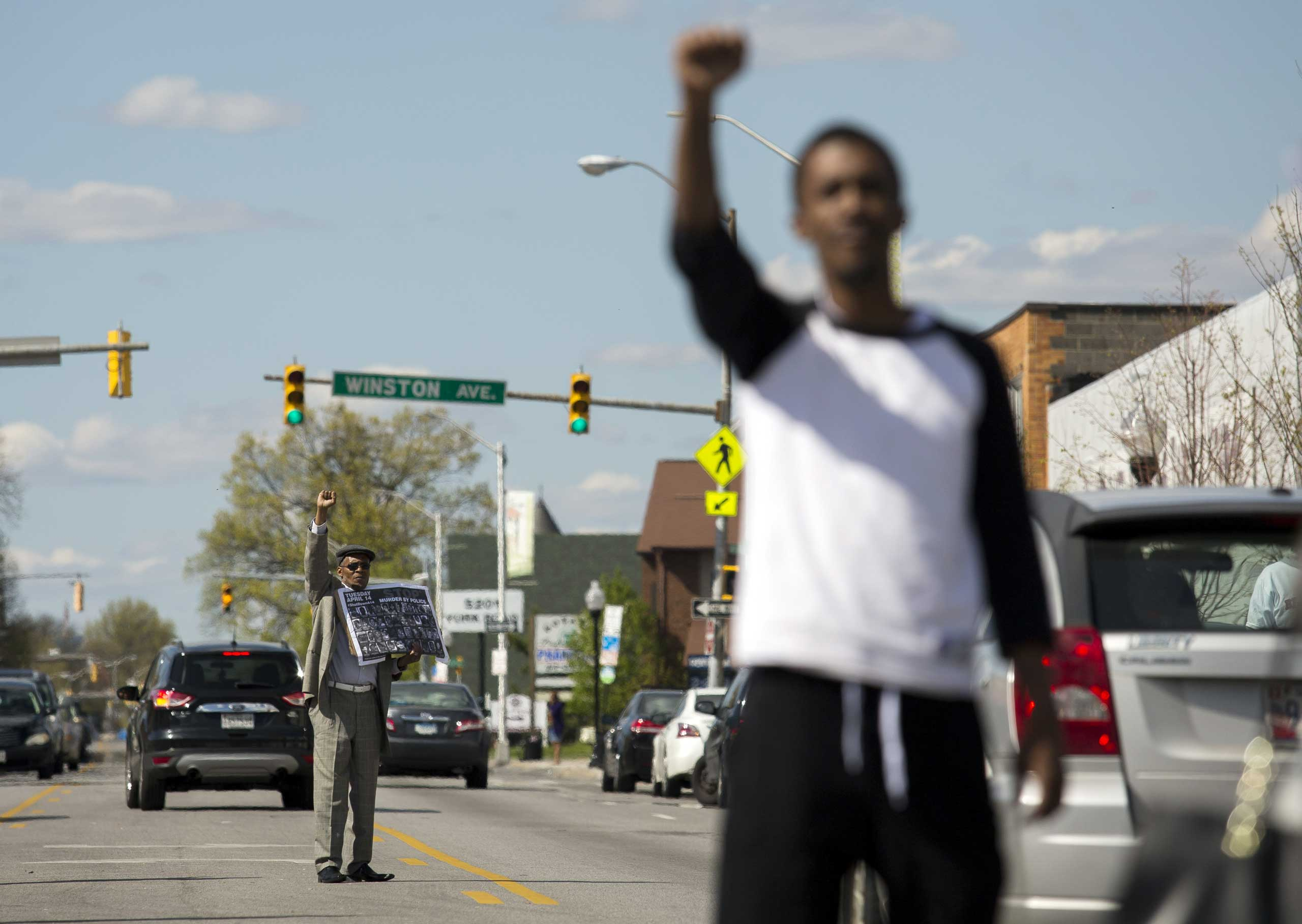 Protestors encourage passing cars to honk while standing in the middle of York Road near Vaughn  Greene Funeral Services during the wake of Freddie Gray in Baltimore on April 26, 2015.