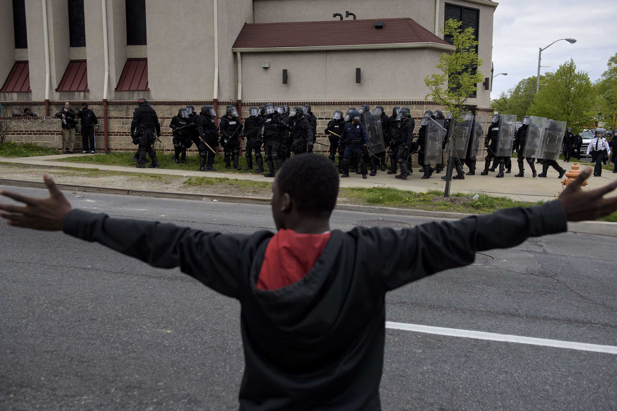 Baltimore police officers form a line in front of protesters near Mondawmin Mall in Baltimore on April 27, 2015.