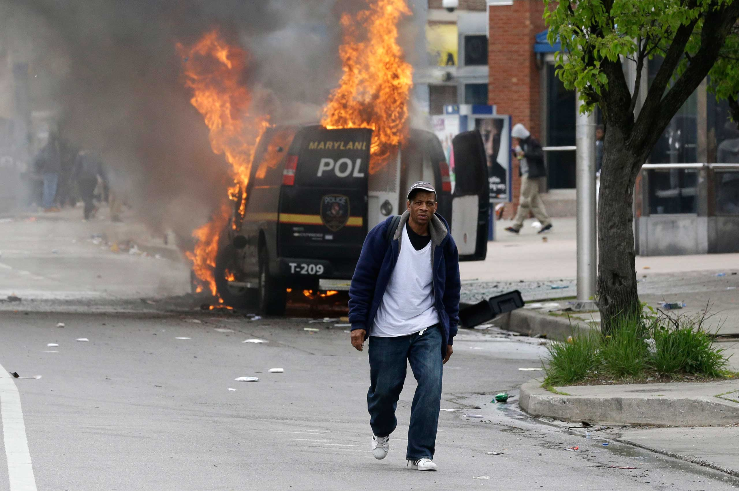 A man walks past a burning police vehicle in Baltimore on April 27, 2015.