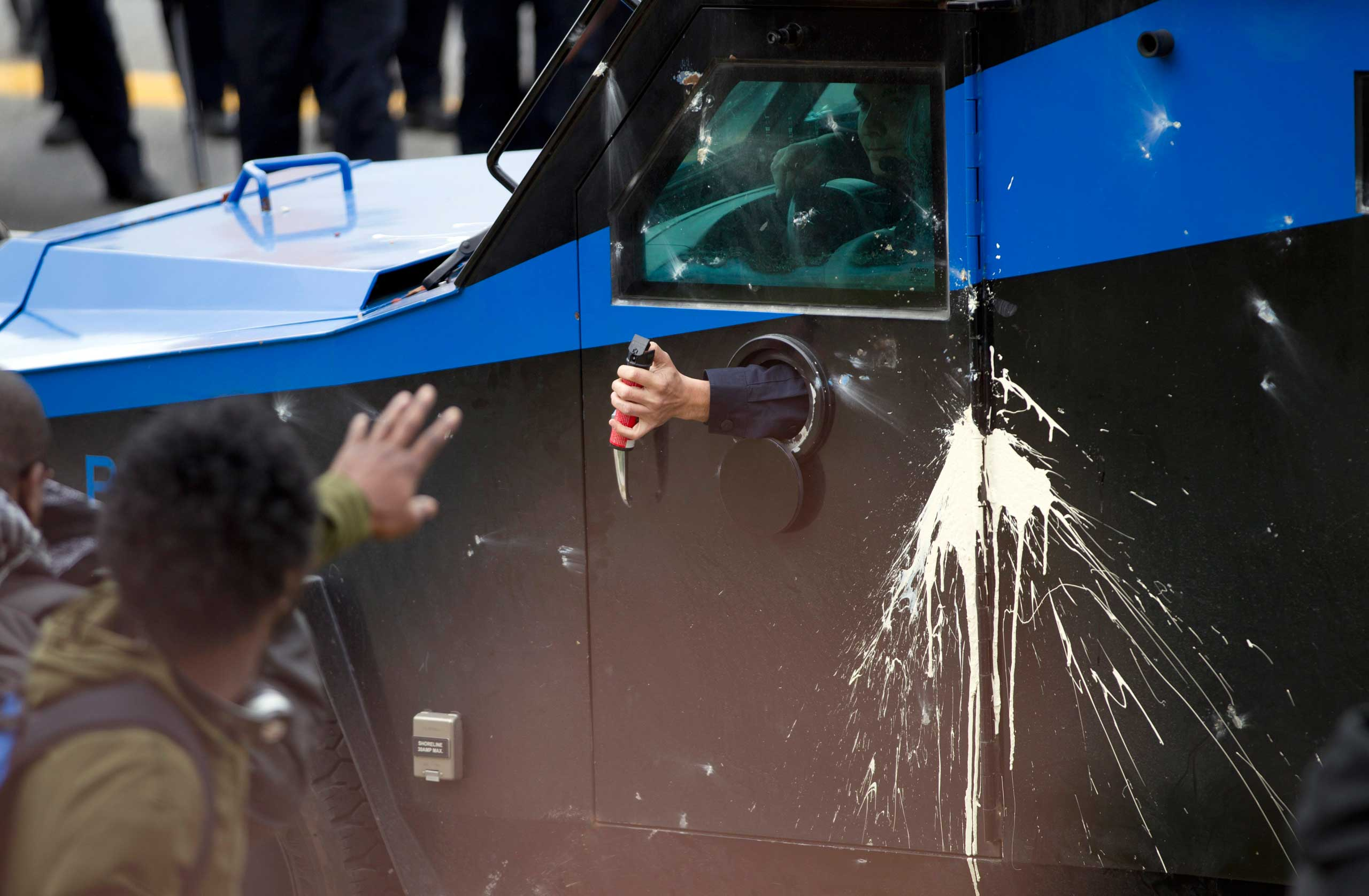 Police officers use pepper spray against demonstrators after the funeral of Freddie Gray in Baltimore on April 27, 2015.