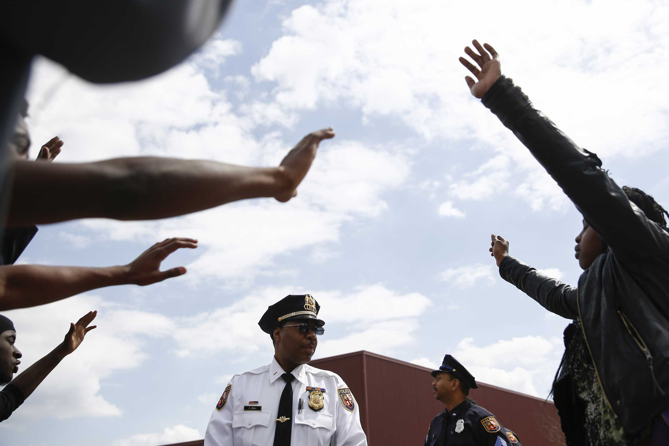 Protesters surround a police officer near Mondawmin Mall in Baltimore on April 27, 2015.