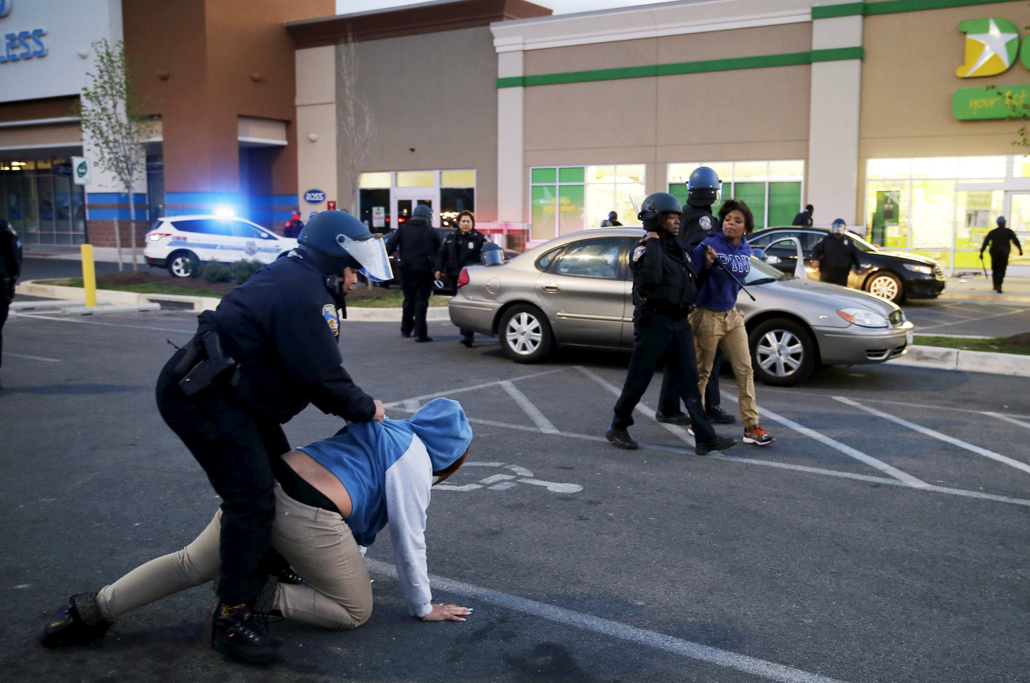 "Baltimore police officers tackle and arrest looters after they emerged from a ""Deals"" store with merchandise during clashes between rioters and police in Baltimore on April 27, 2015."