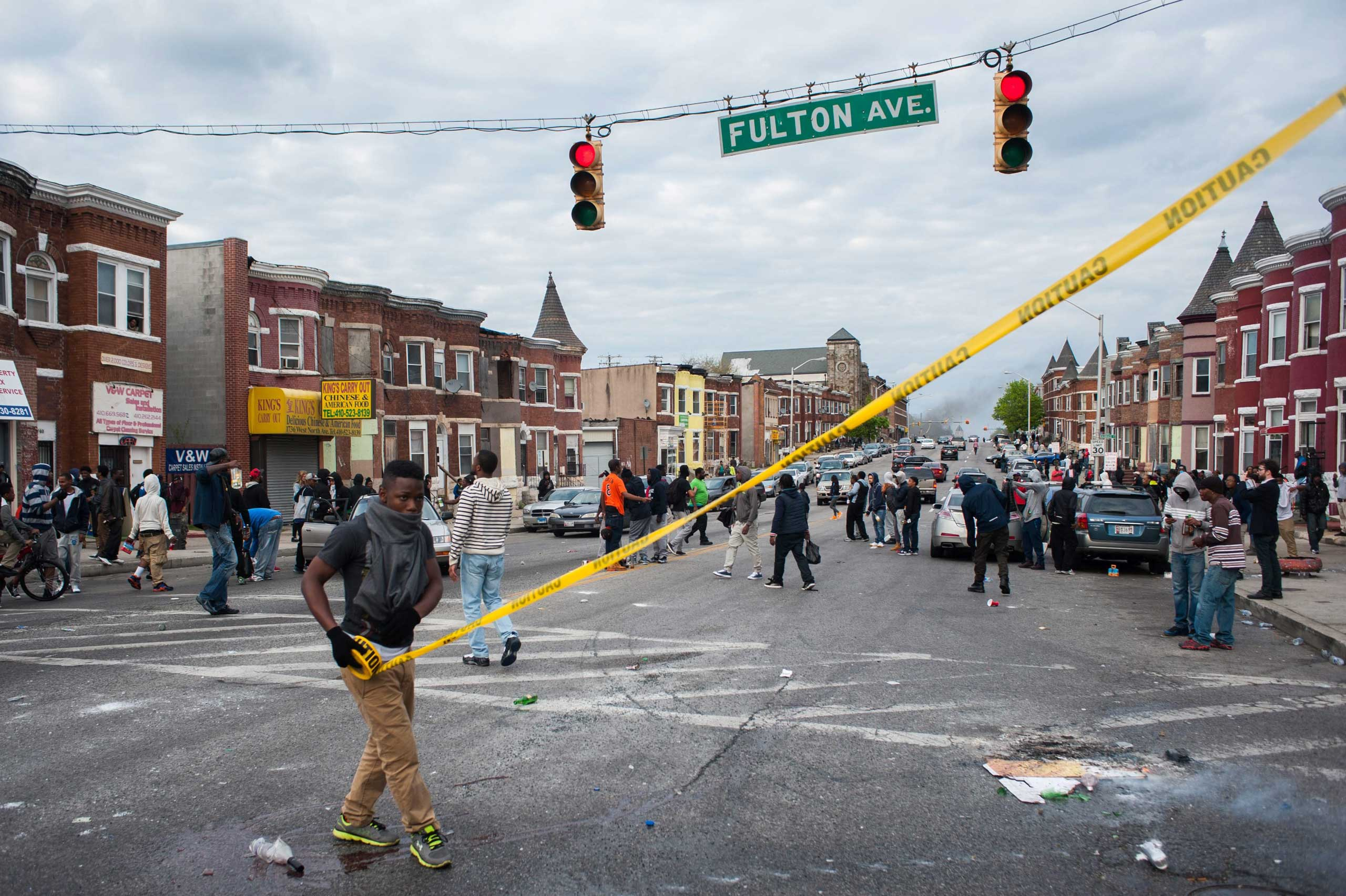 A protestor unrolls police caution tape on North Avenue and Fulton Street during a protest for the death of Freddie Gray in Baltimore on April 27, 2015.