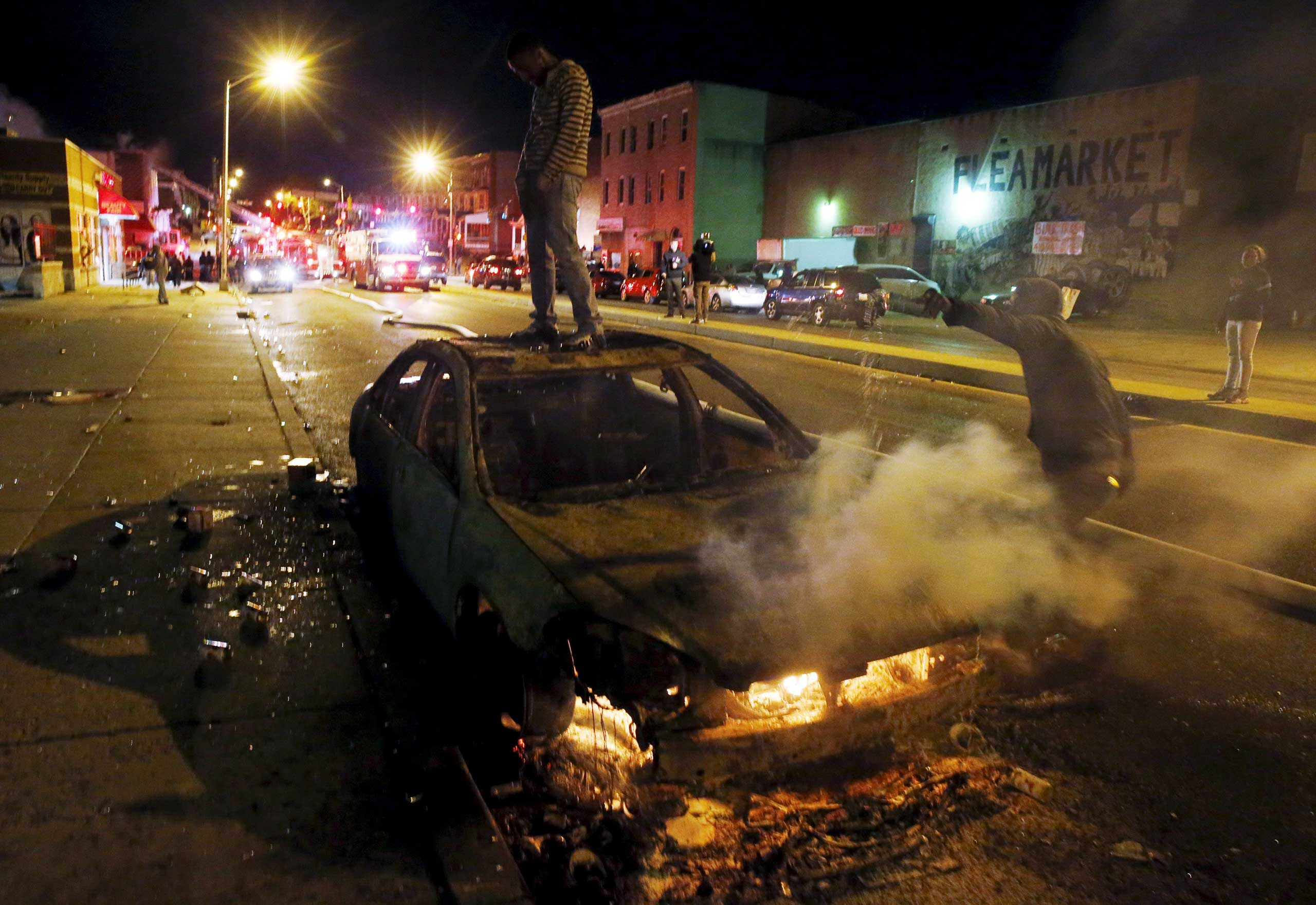 A rioter stands atop a burning car as another man pours fuel onto the fire while Baltimore firefighters behind them fight fires in multiple burning buildings set ablaze by rioters during clashes in Baltimore on April 27, 2015.