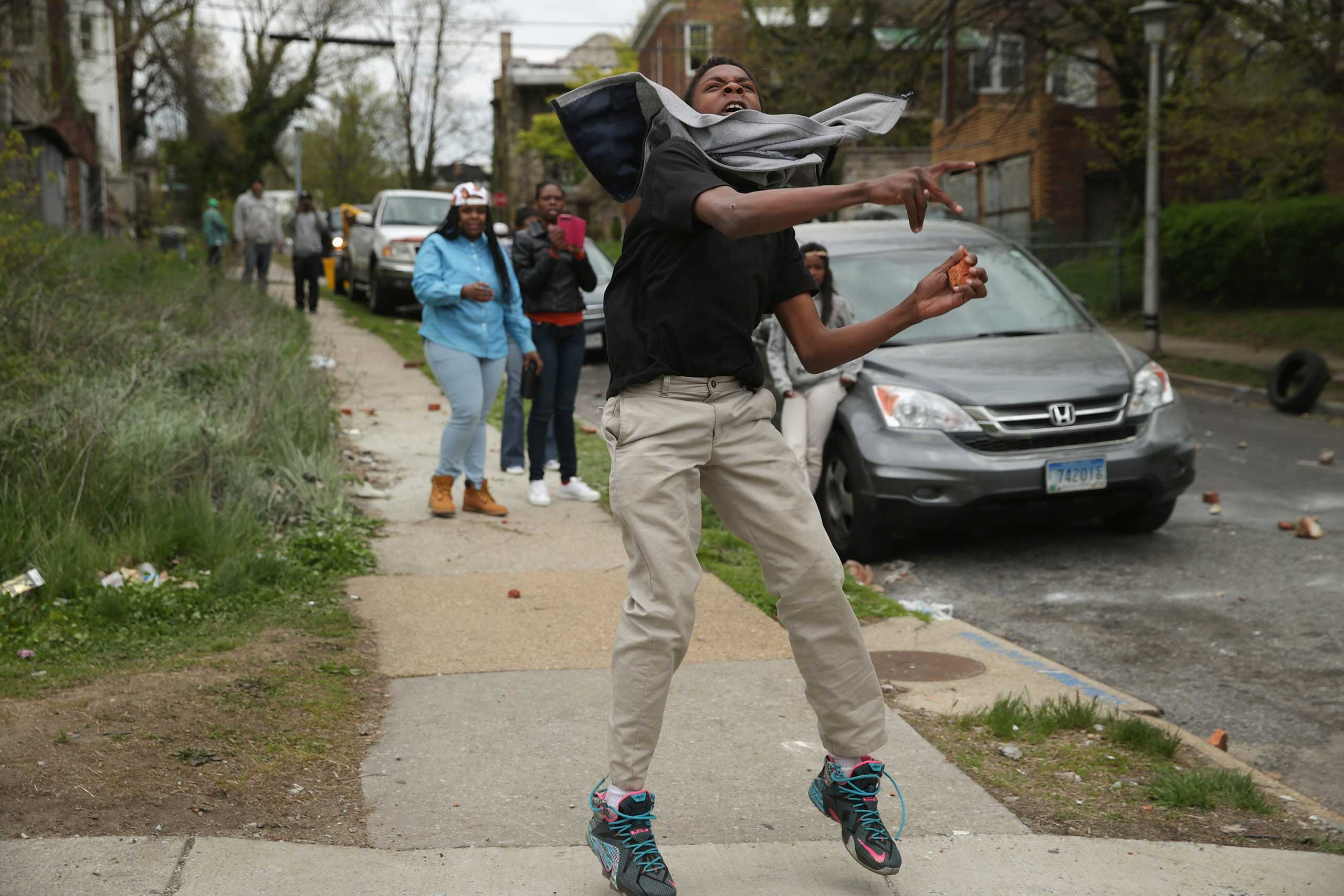 A man hurls a rock at Baltimore police officers outside the Mondawmin Mall following the funeral of Freddie Gray in Baltimore on April 27, 2015.