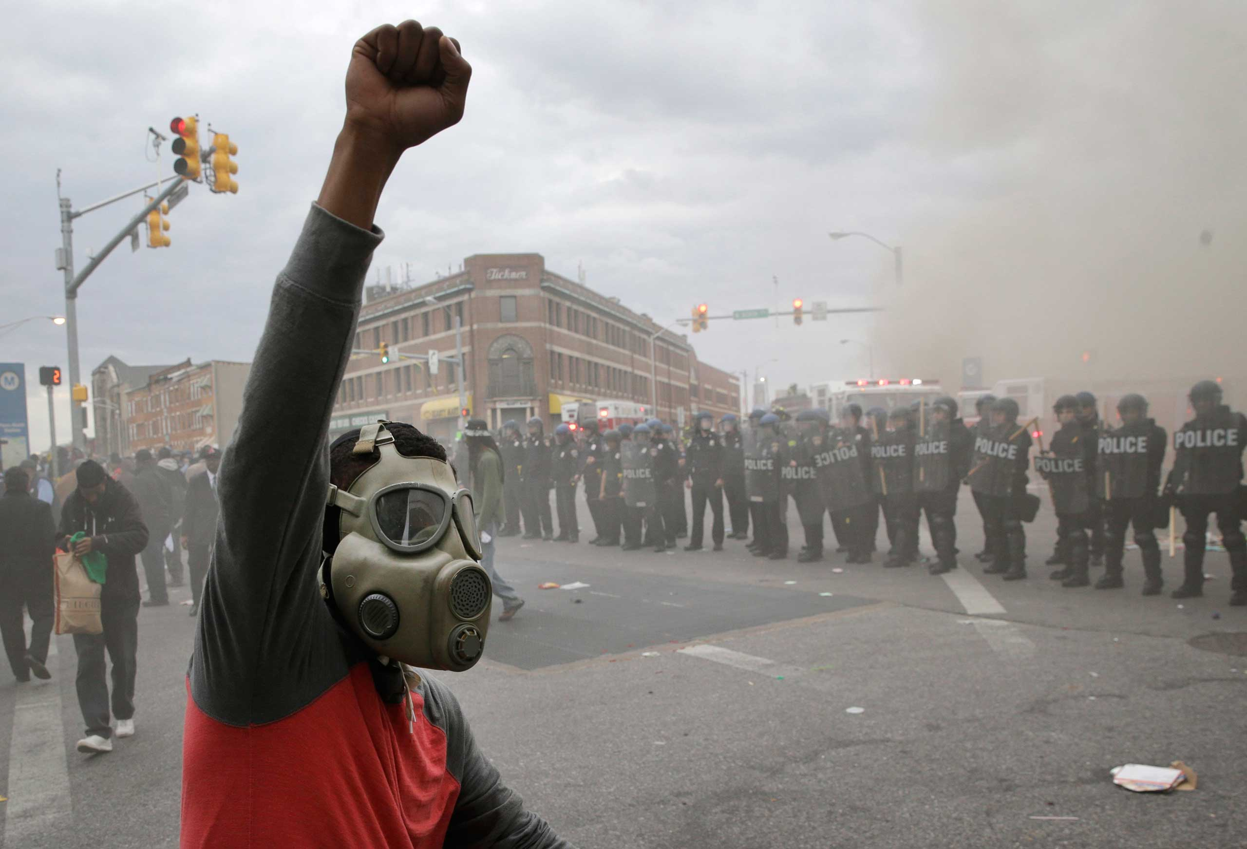 A demonstrator raises his fist as police stand in formation as a store burns during unrest following the funeral of Freddie Gray in Baltimore on Monday, April 27, 2015.