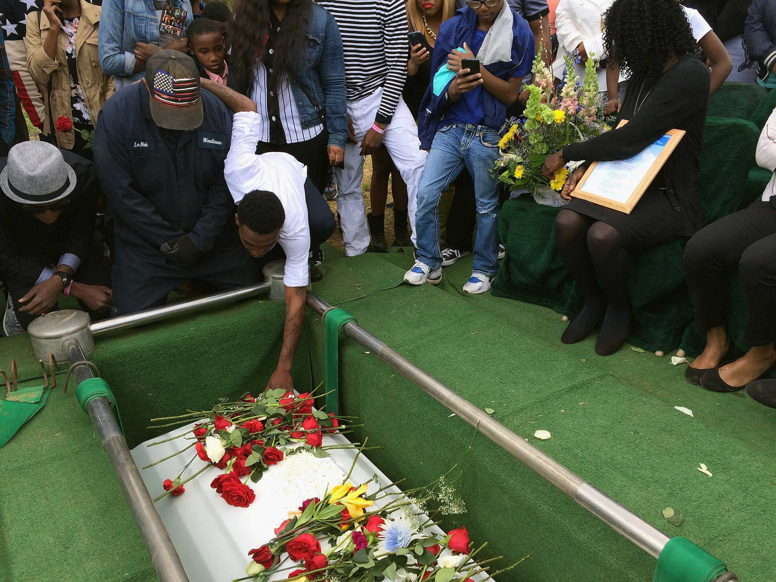 Friends and relatives say their last goodbyes to Freddie Gray as his casket is lowered into his grave at the Woodland Cemetery in Baltimore on April 27, 2015.