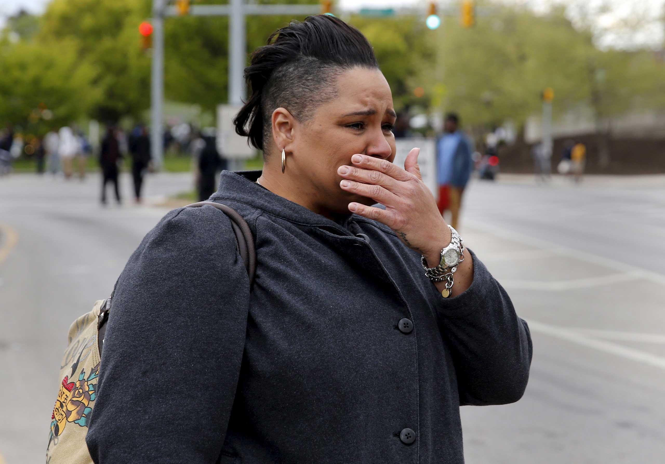 A woman cries as demonstrators throw rocks at police officers during clashes in Baltimore on April 27, 2015.