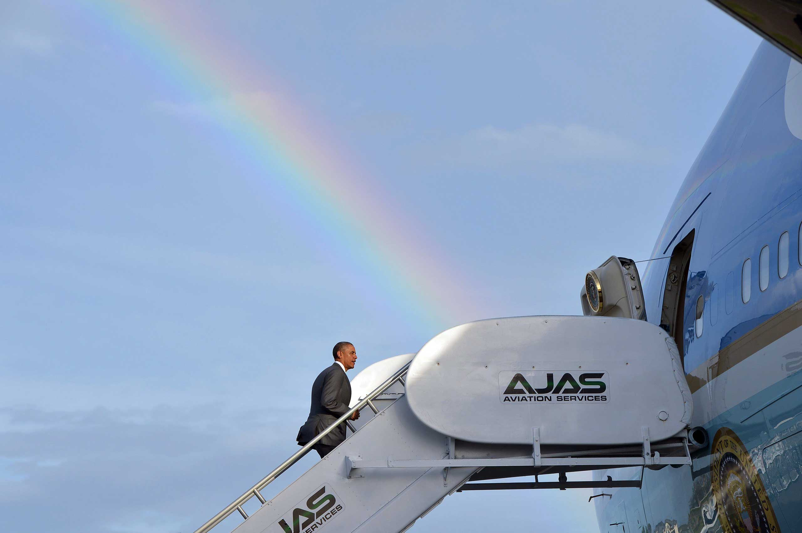 US President Barack Obama makes his way to board Air Force One under a rainbow upon departure from Kingston, Jamaica on April 9, 2015.