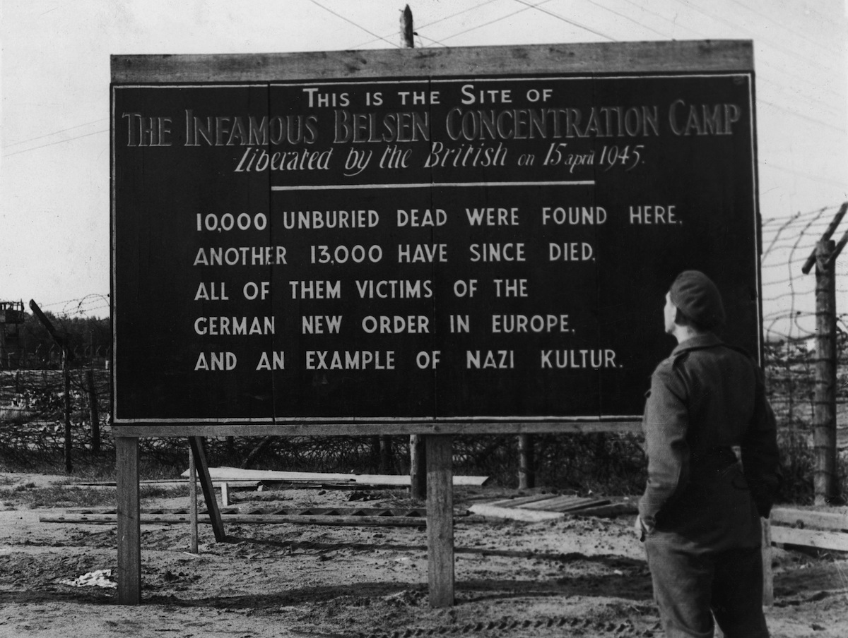A British soldier reads a billboard posted at the entrance of the Belsen concentration camp, Belsen, Germany