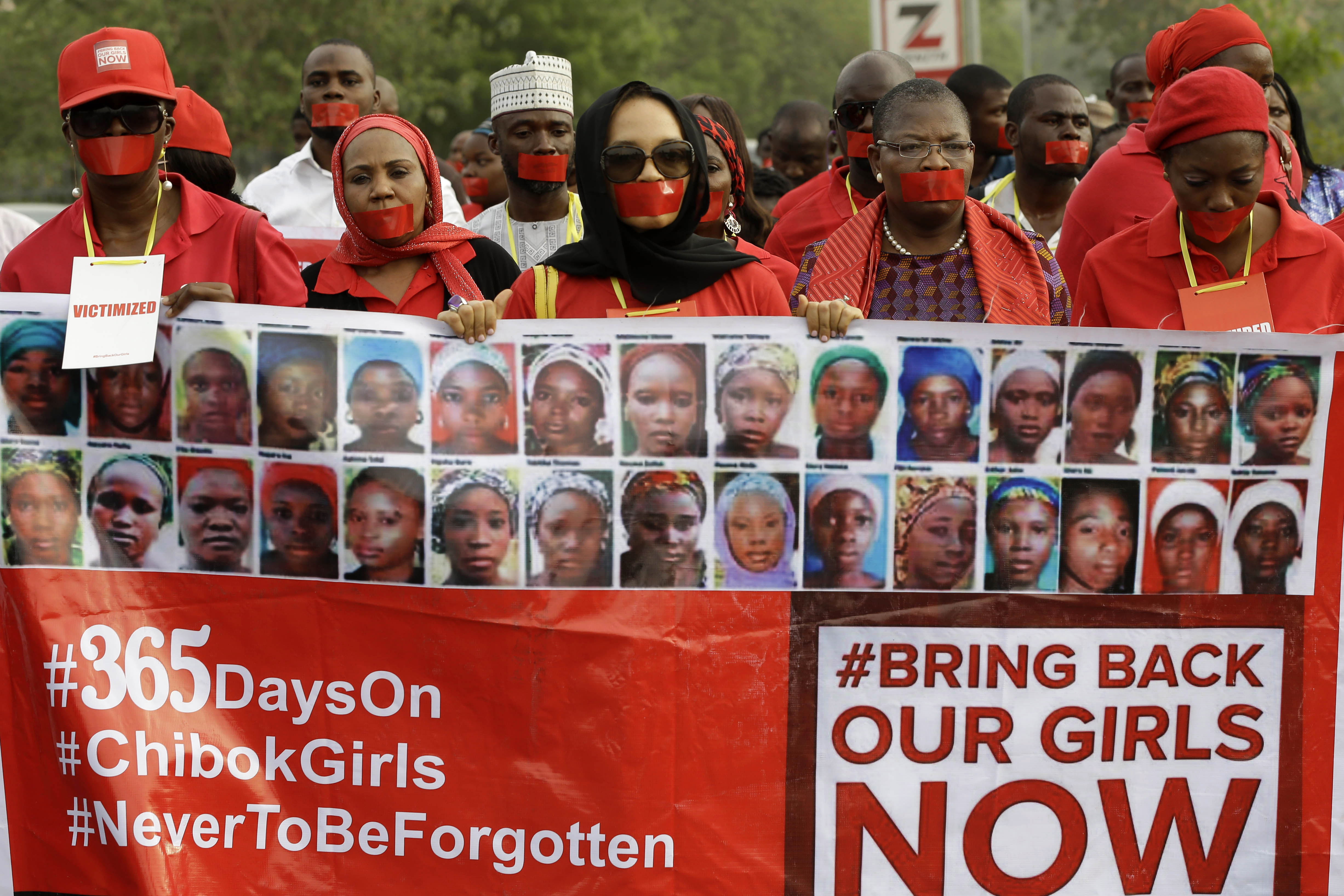 People march on a street of Abuja, Nigeria, during a silent protest on April 13, 2015, calling on the government to rescue the Chibok schoolgirls who were kidnapped a year ago