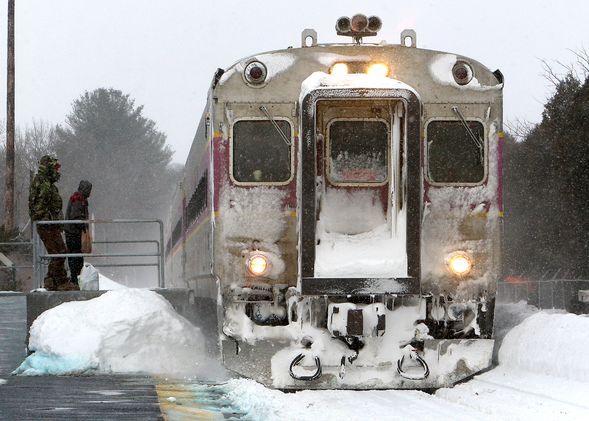 Passengers wait as MBTA commuter rail train pulls into the North Beverly station in Beverly, Mass. Feb. 17, 2015, running on a special storm schedule because of the snow.