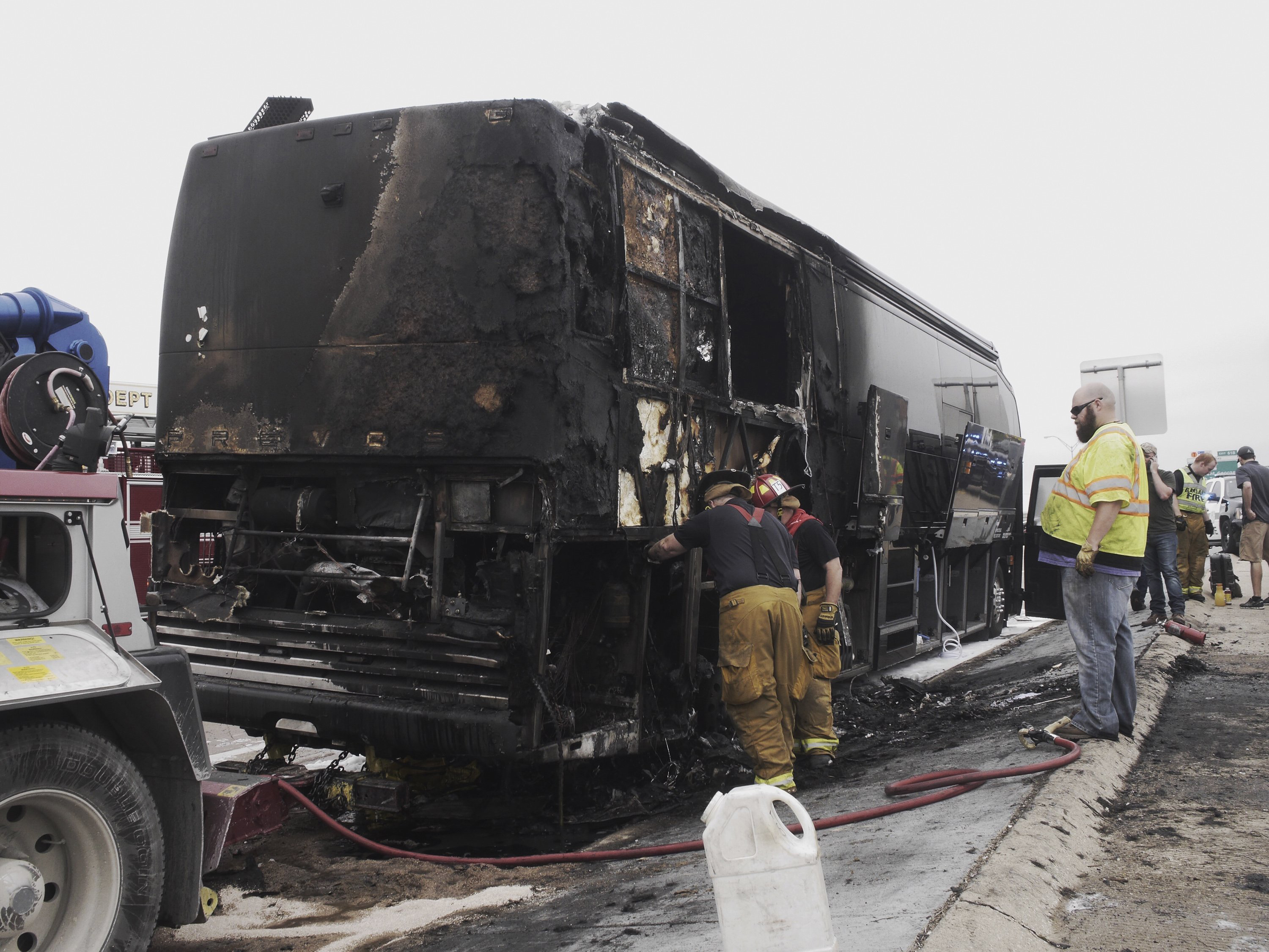 Firemen look at the damage after a fire on county music group Lady Antebellum's bus on eastbound I-30 in Garland, Texas, April 16, 2015.