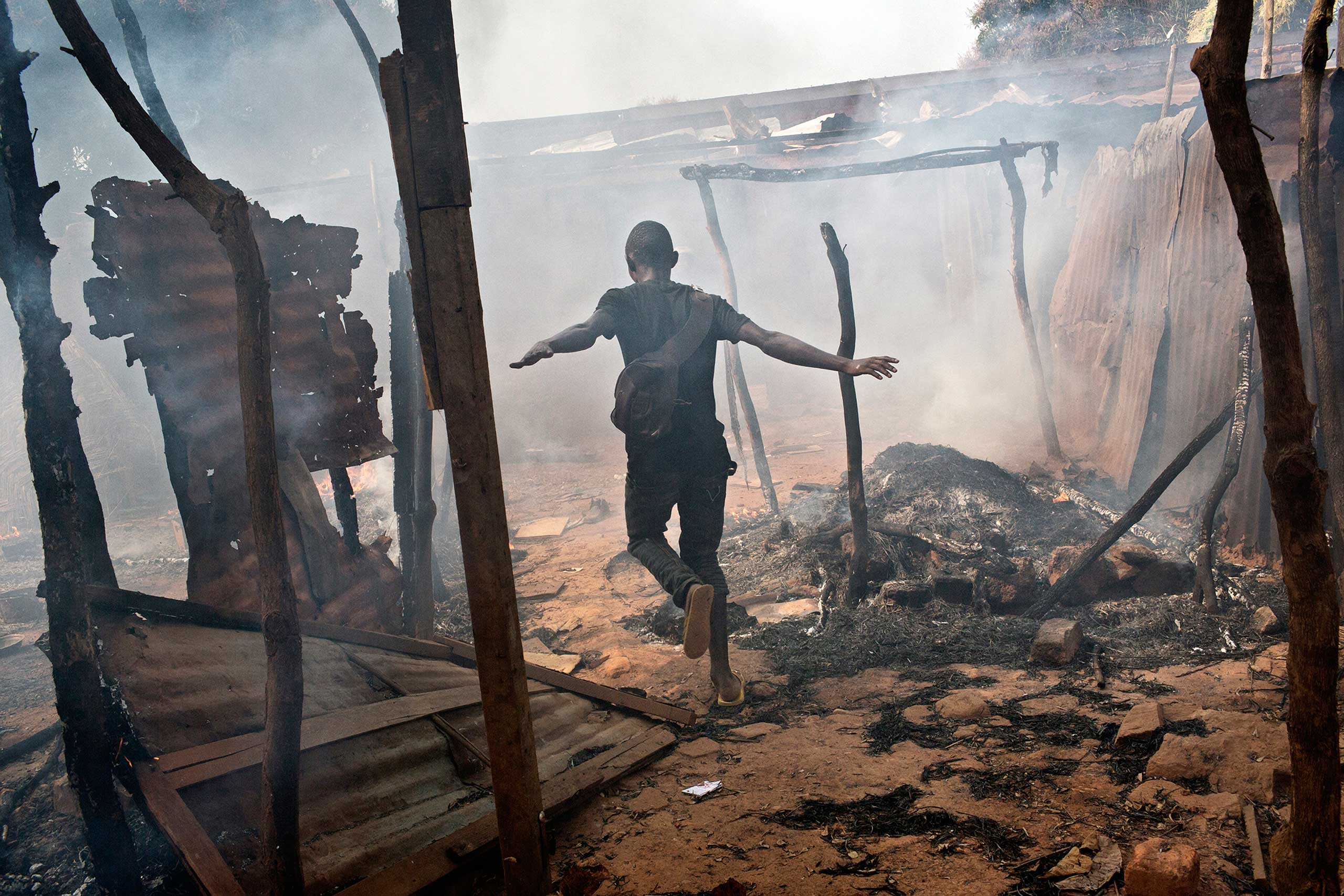 A member of the Christian population around PK13 on the outskirts of Bangui runs through looted and burning homes of the Muslims who have fled after the Seleka President Michel Djotodia resigned and left the country in disarray The country was ruled by a minority Muslim government after the coup in March 2013. After months of oppression by the Muslim Seleka Government the local population take out their anger and frustrations on the largely innocent Muslim population.