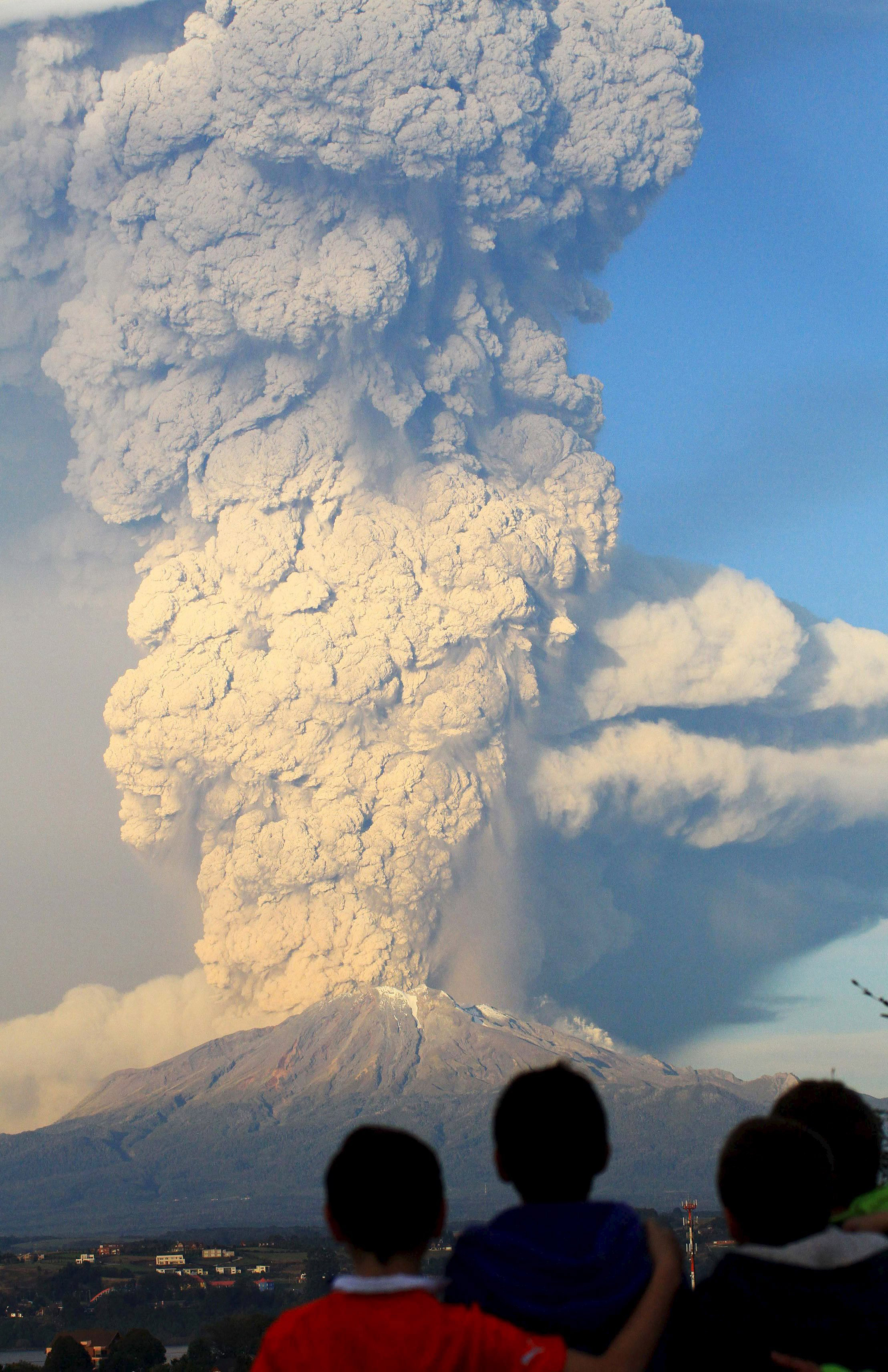 Children from Puerto Varas look on as ash rises from the Calbuco volcano on April 22, 2015.