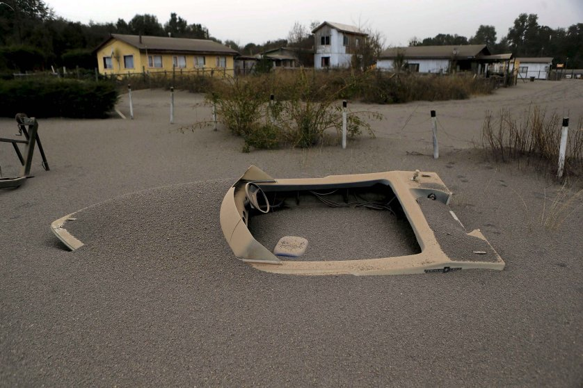 An ash-covered boat sits in the backyard of a home just north of the Calbuco volcano