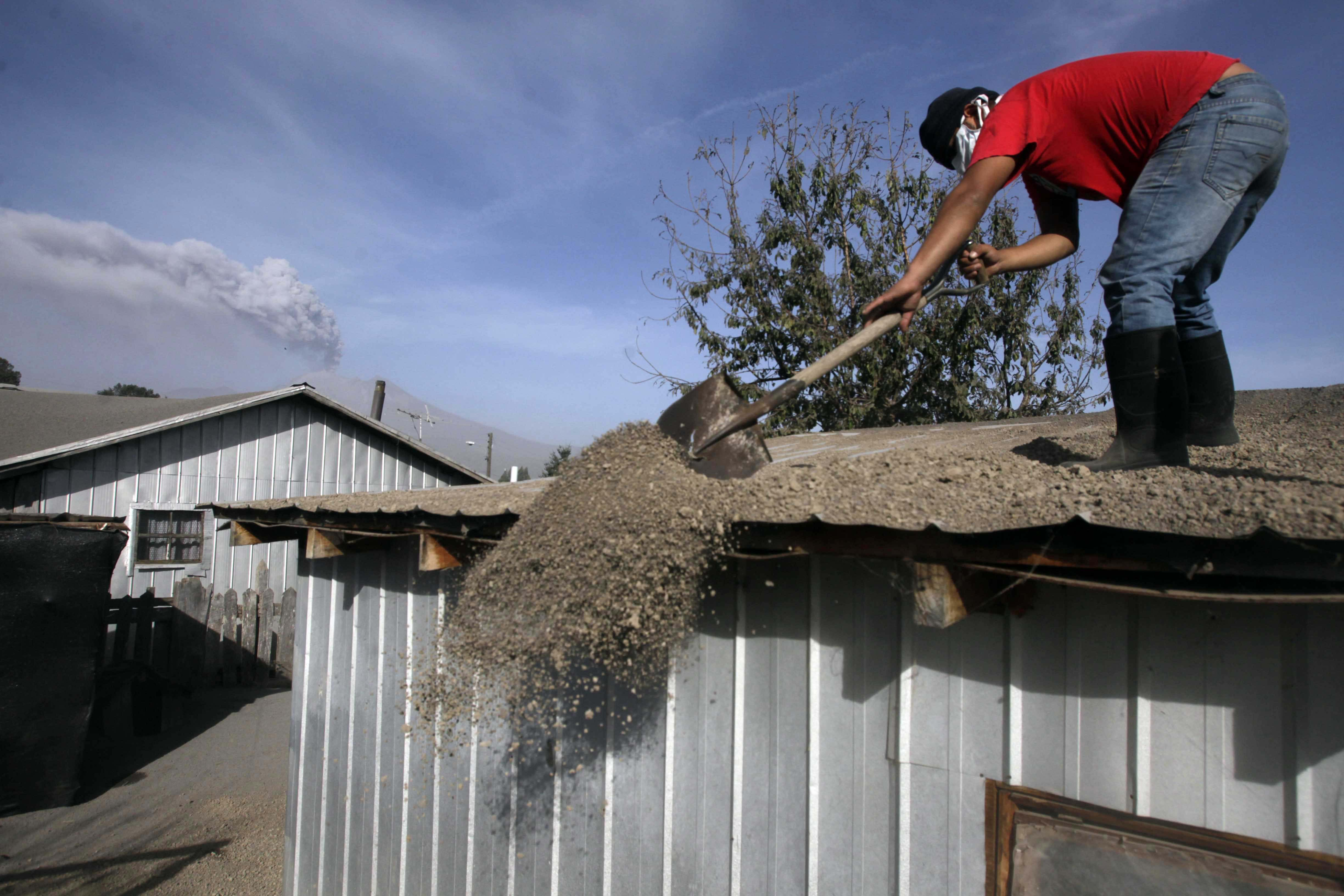A man sweeps volcanic ash from the rooftop of his home in Puerto Varas, Chile, April 24, 2015.