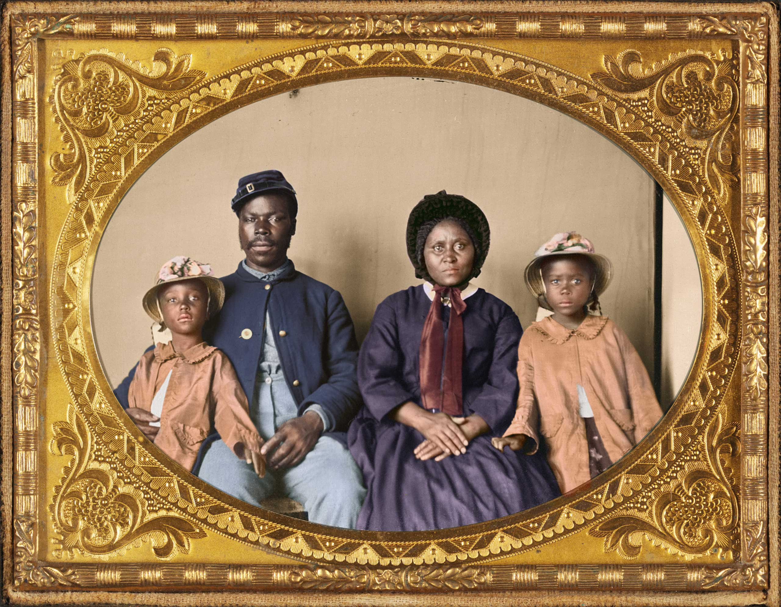 Unidentified African American soldier in Union uniform with wife and two daughters, 1863-1865.