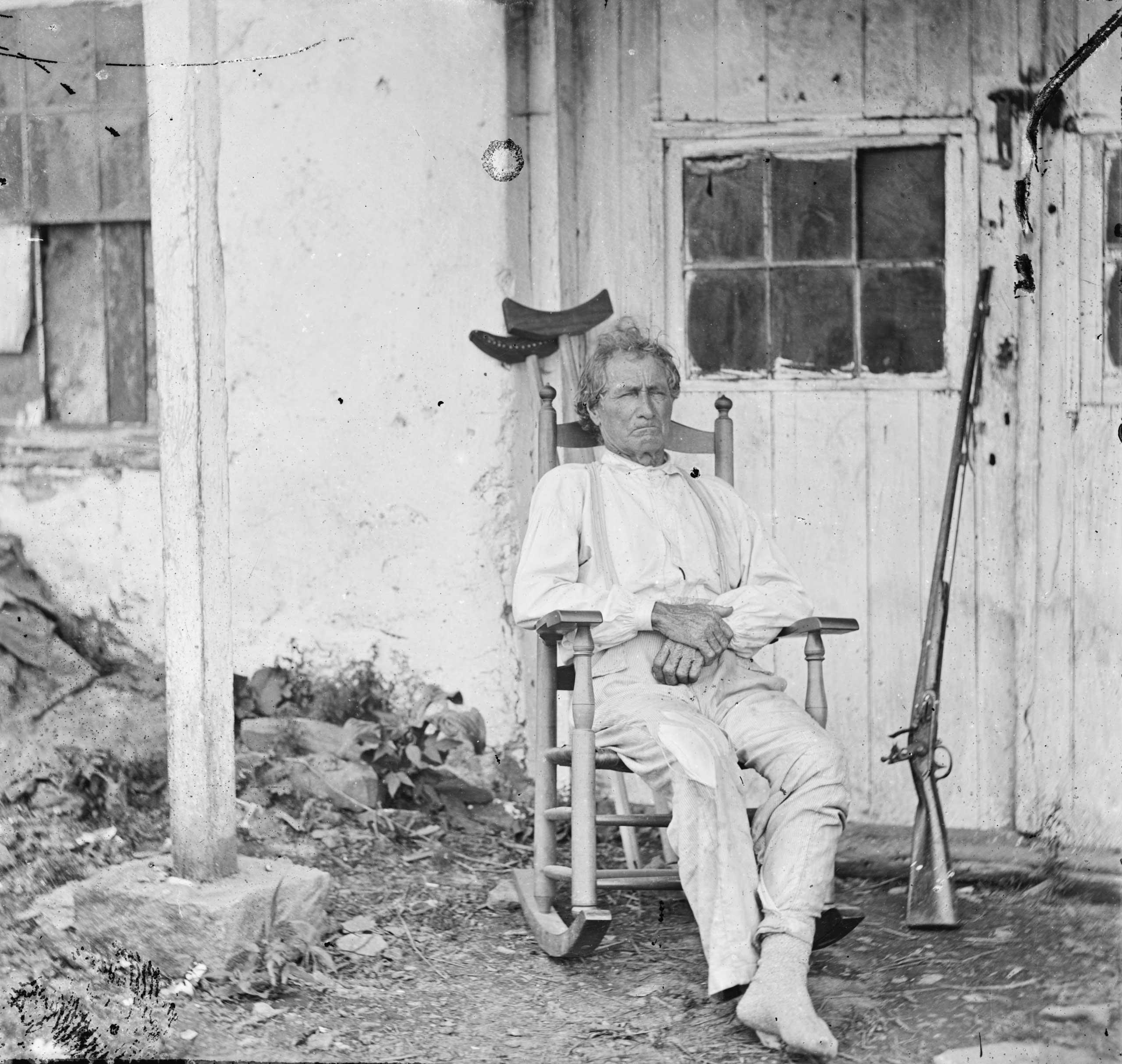 "John L. Burns, the ""old hero of Gettysburg,"" with gun and crutches in Gettysburg, Penn., July, 1863."