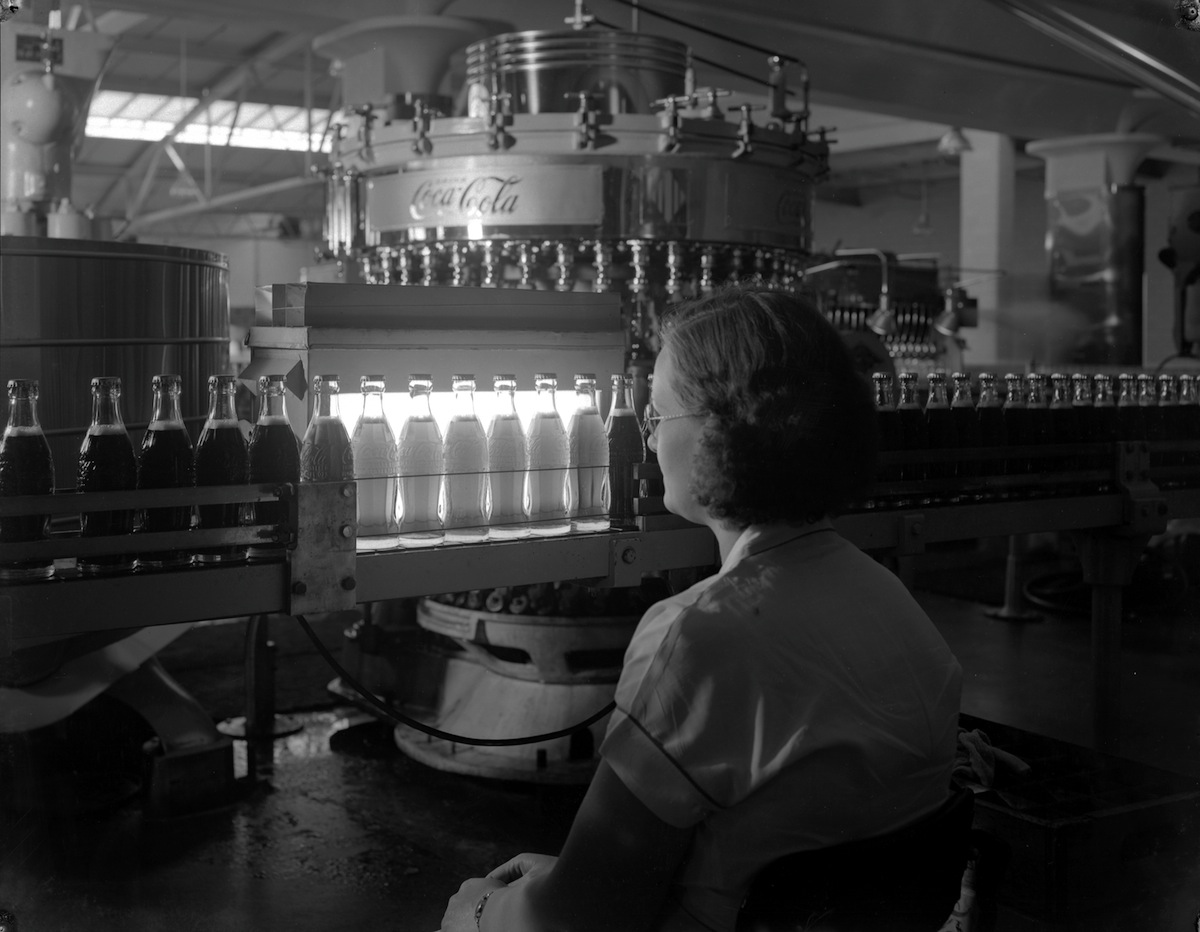 An inspector scrutinizes bottles of Coca-Cola as they pass in front of a piercing light, in Cincinnati, Ohio, in the 1940s