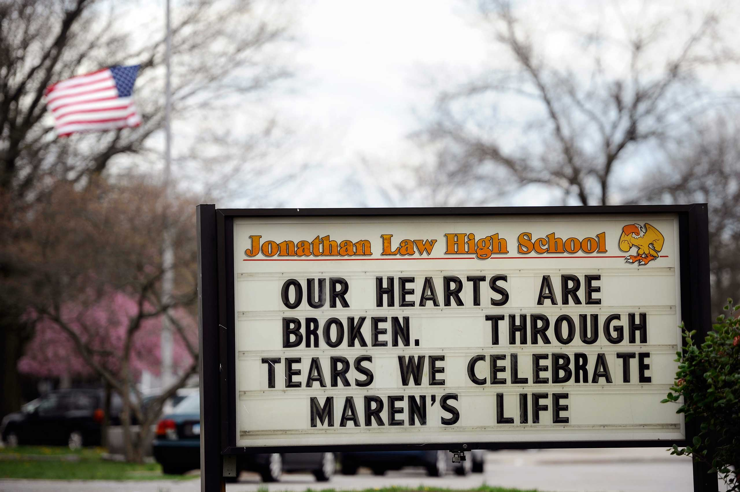A sign at the entrance to Jonathan Law High School memorializes Maren Sanchez as a flag at half-staff blows in the distance on school grounds in Milford, Conn., on May 2, 2014.