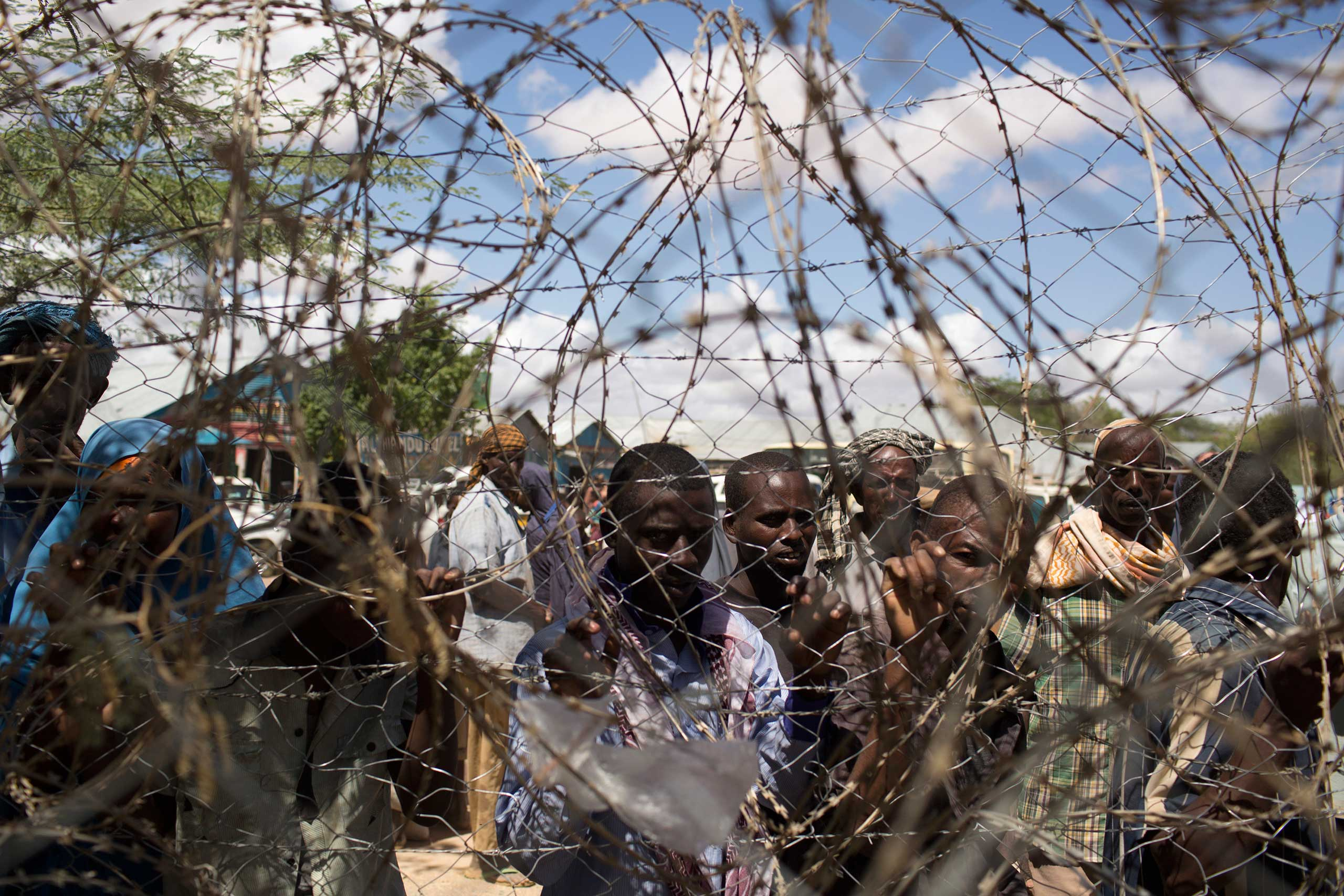 Somali refugees look through a barbwire fence in Dagahale, one of the several refugee settlements in Dadaab, Garissa County, northeastern Kenya in 2013.