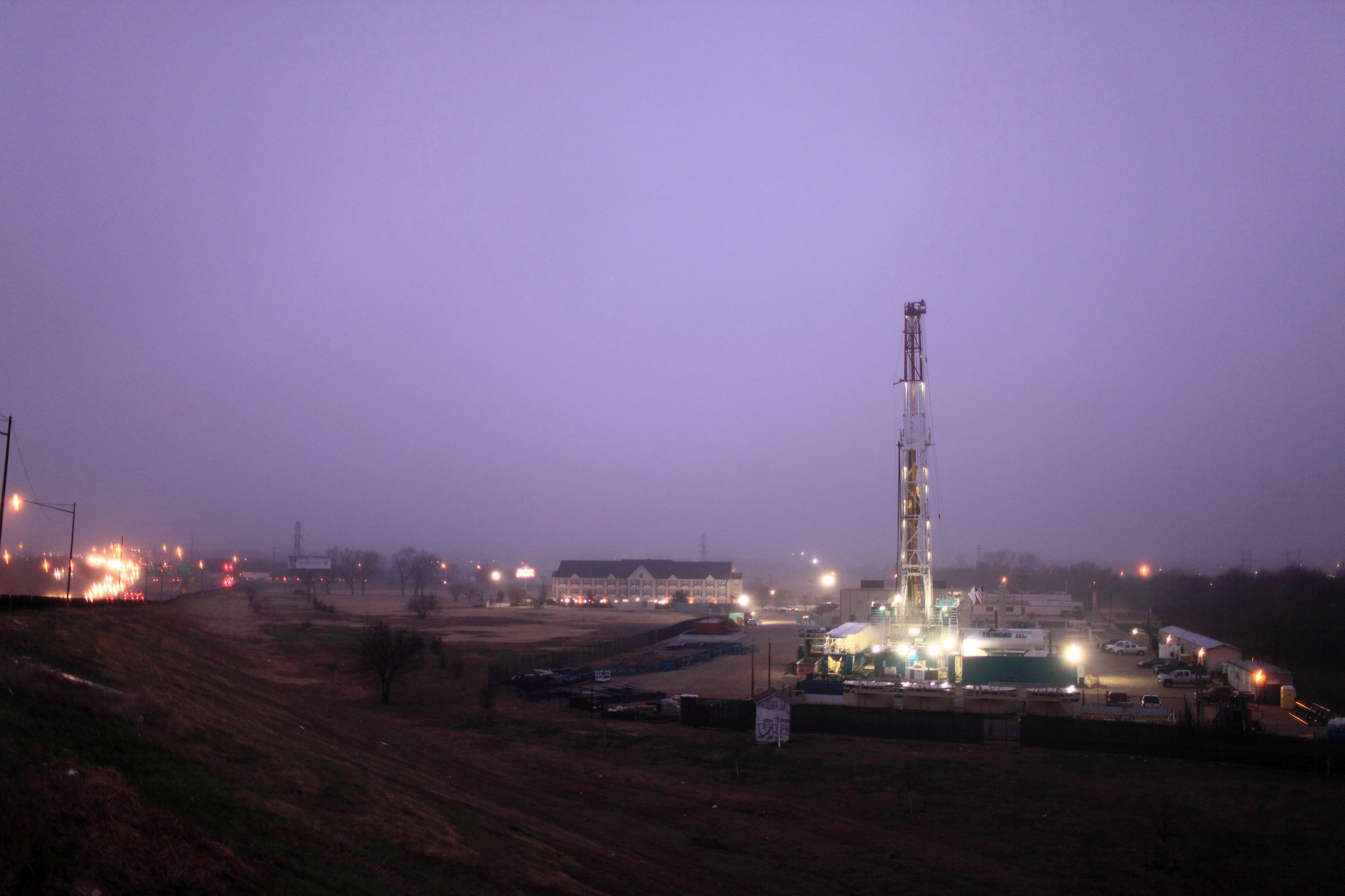 A 150-foot derrick towers over traffic along Interstate 35W, left, positioned on a natural gas well site in Fort Worth, Texas.