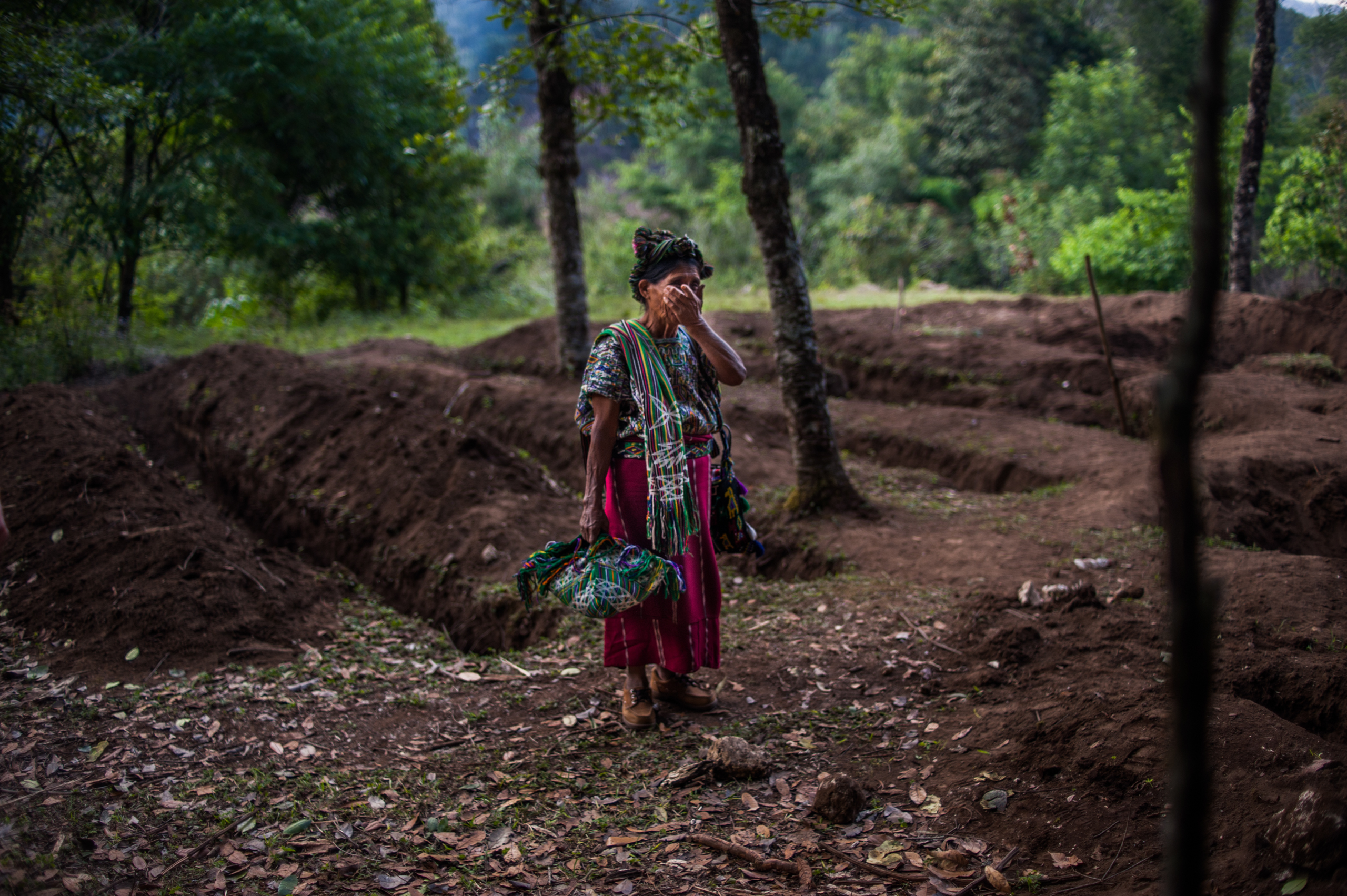 Feliciana Bernal stands between the trenches dug by forensic anthropologists in Xe'Xuxcap, Nebaj. She is looking for her one year-old son, who died over 30 years ago.