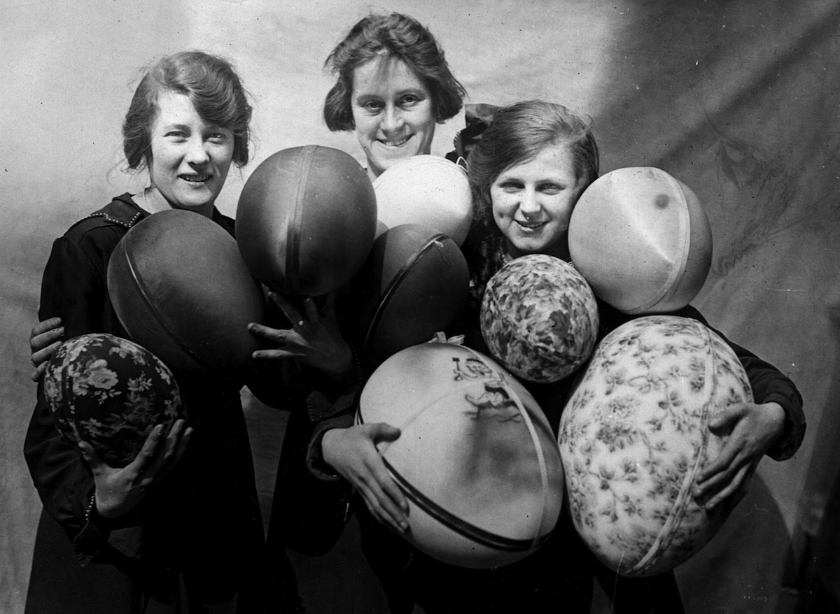Three women holding armfuls of large Easter eggs, circa 1925
