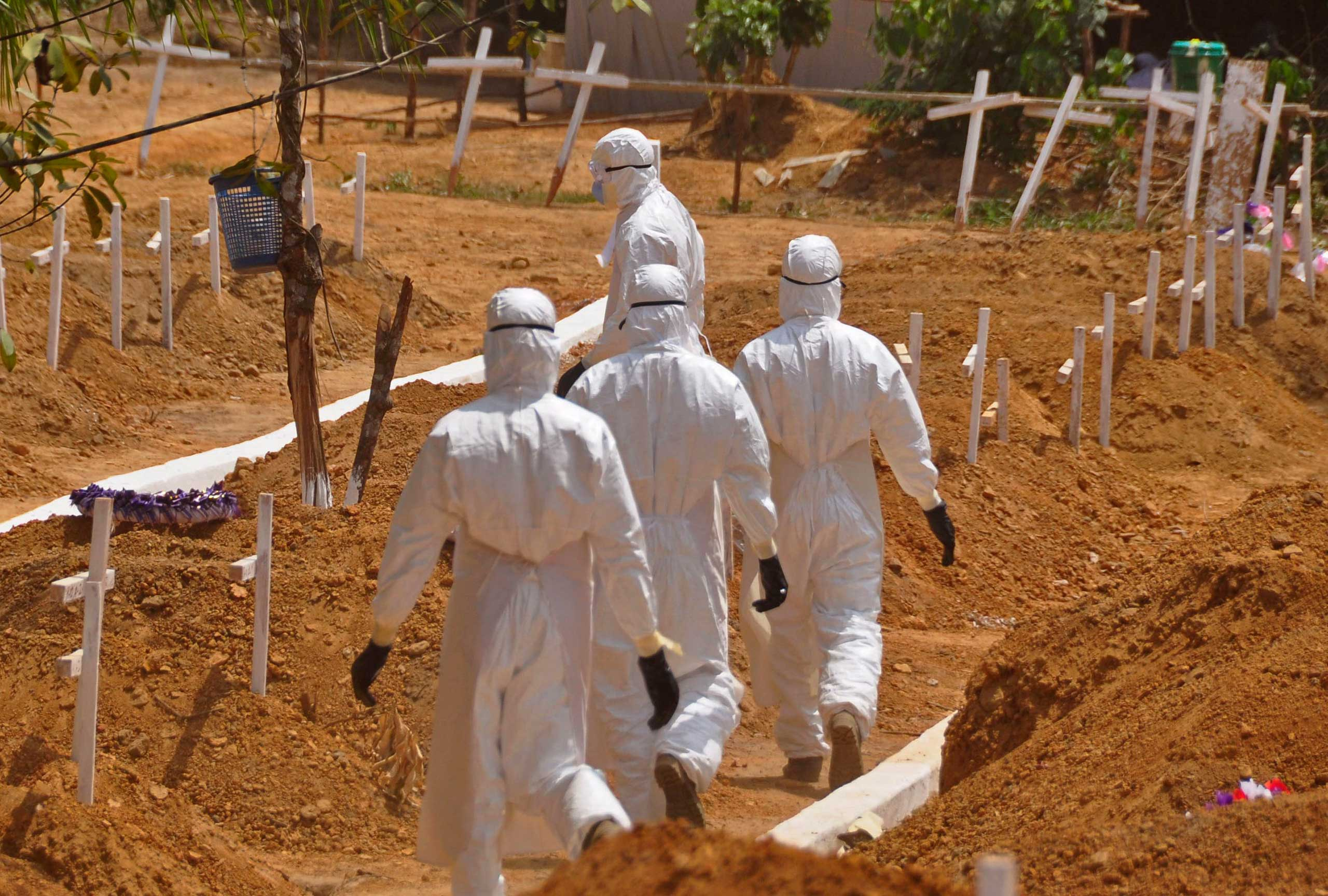 Health workers walk inside a new graveyard for Ebola victims, on the outskirts of Monrovia, Liberia on March 11, 2015.