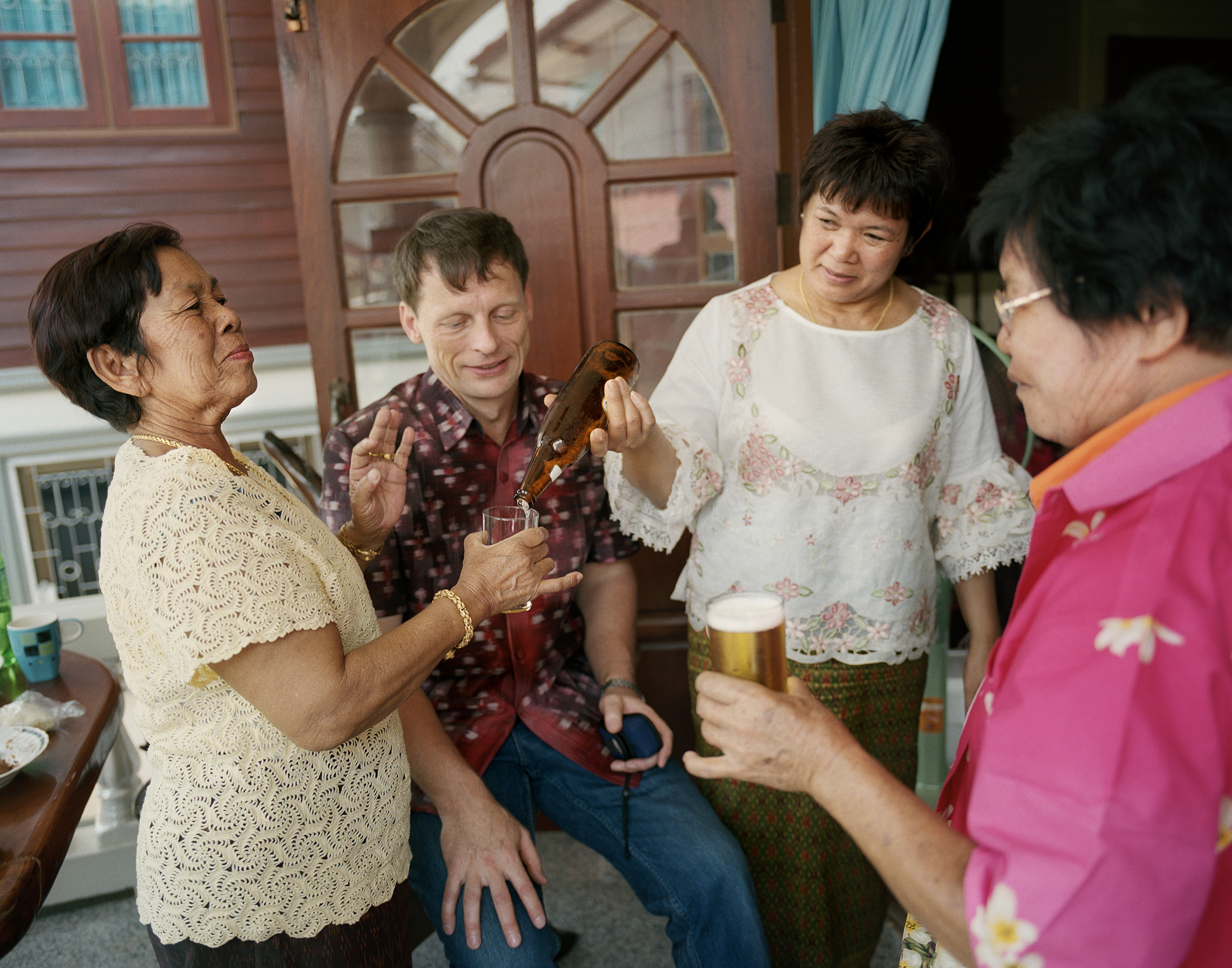 Sombat serves beer to her cousin during a party at the family's home, Kaeng Khro, 2010.