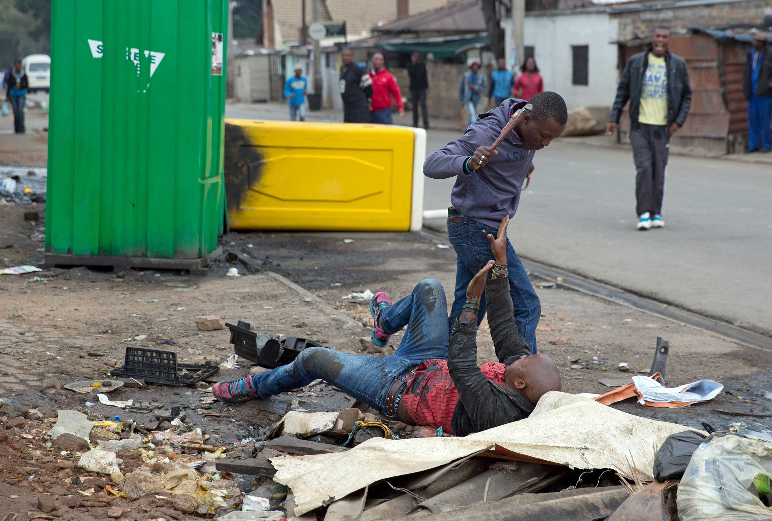 Sithole is attacked by men in Alexandra township during anti-immigrant violence in Johannesburg on April 18, 2015.