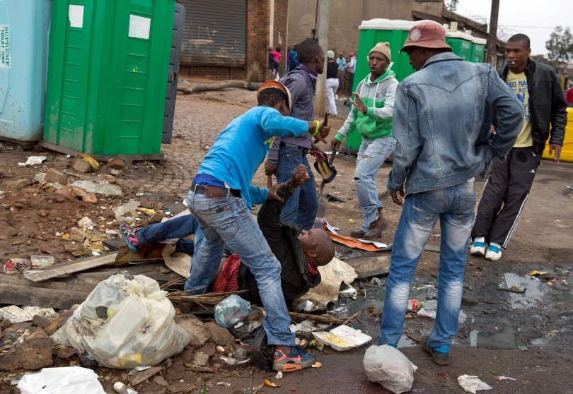 Mozambique national Emmanuel Sithole is attacked by men in Alexandra township during anti-immigrant violence in Johannesburg on April 18, 2015.