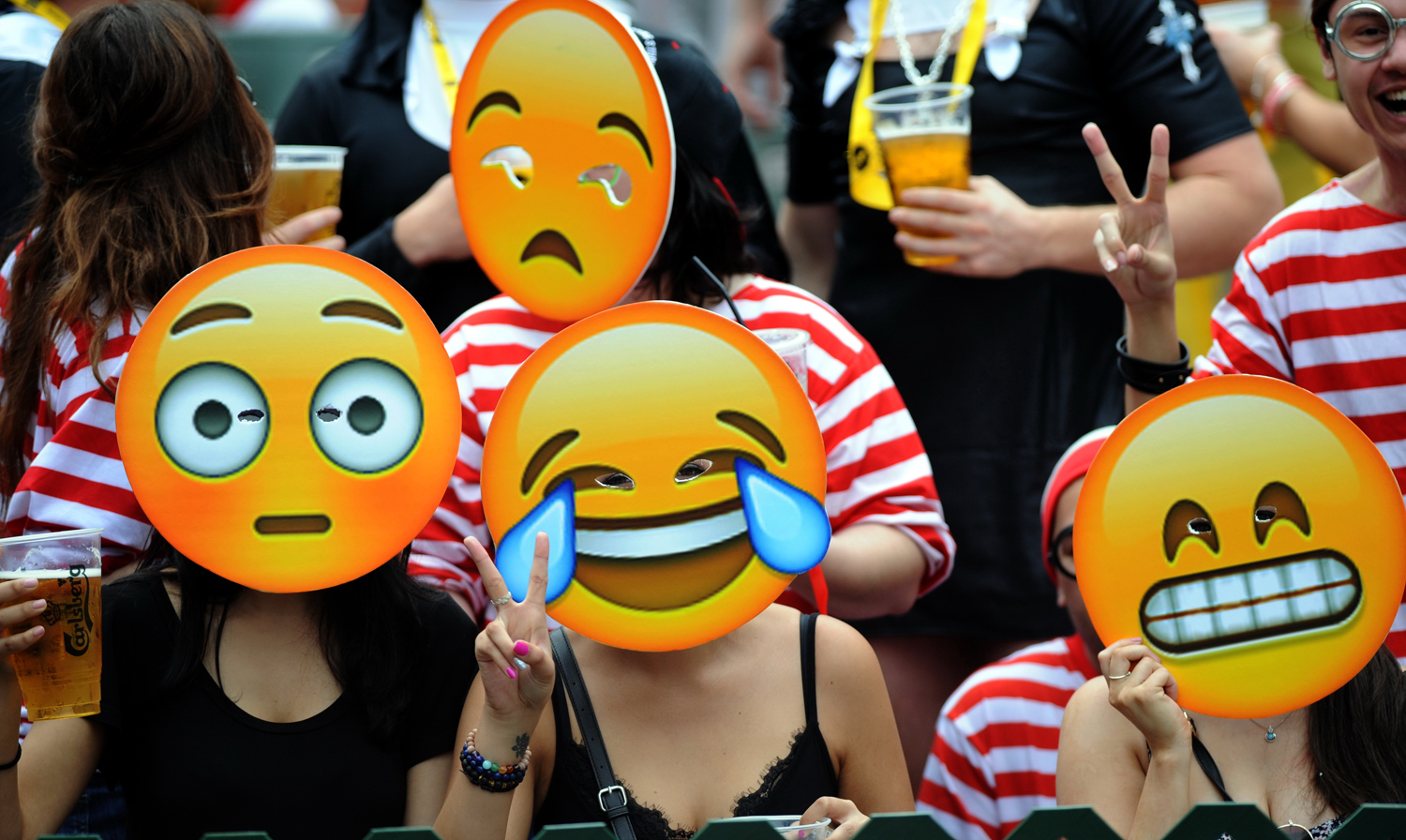 Fans wearing emoji masks watch a rugby match of the Hong Kong Seven in Hong Kong on March 28, 2015