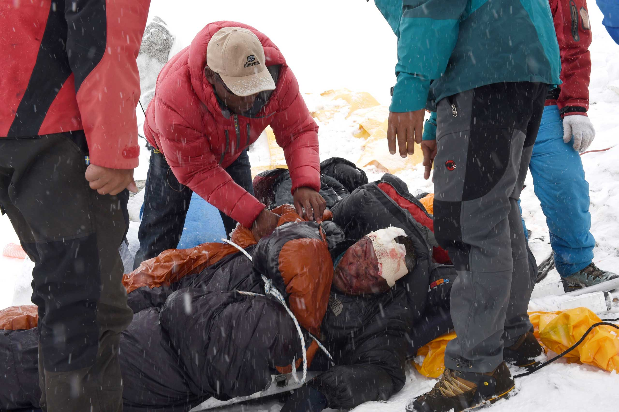 Rescuers tend to an injured sherpa after the avalanche that was triggered by an earthquake outside Kathmandu, Nepal, on April 25, 2015.