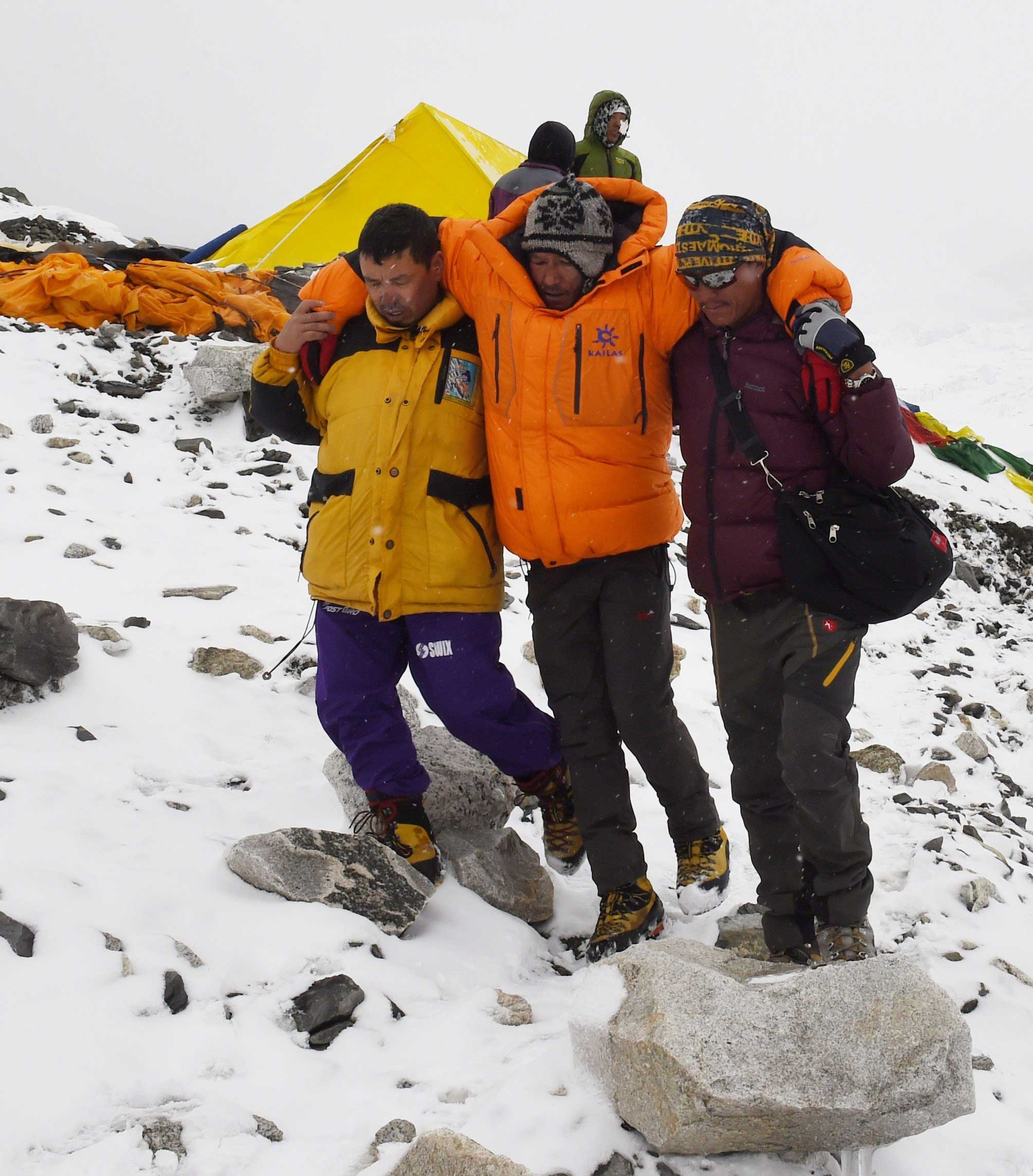 Rescuers assist an injured person at Everest Base Camp after an avalanche was triggered by an earthquake outside Kathmandu, Nepal, on April 25, 2015.