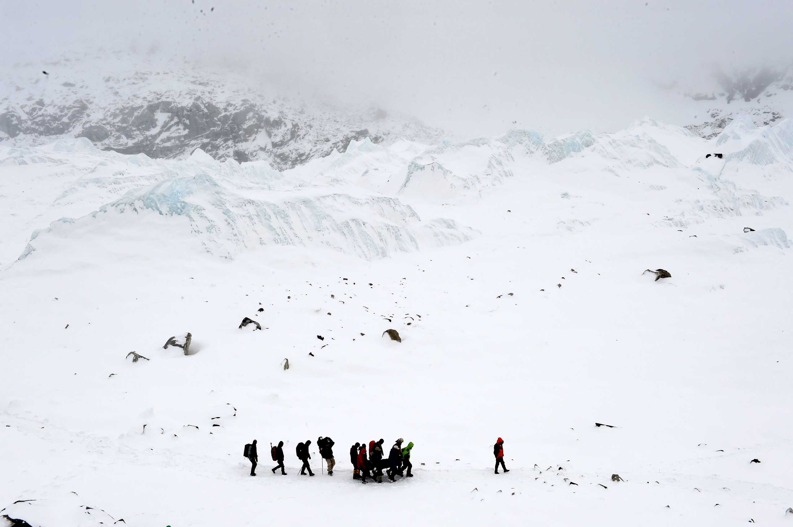 Rescuers carry an injured sherpa after the avalanche that was triggered by an earthquake outside Kathmandu, Nepal, on April 25, 2015.