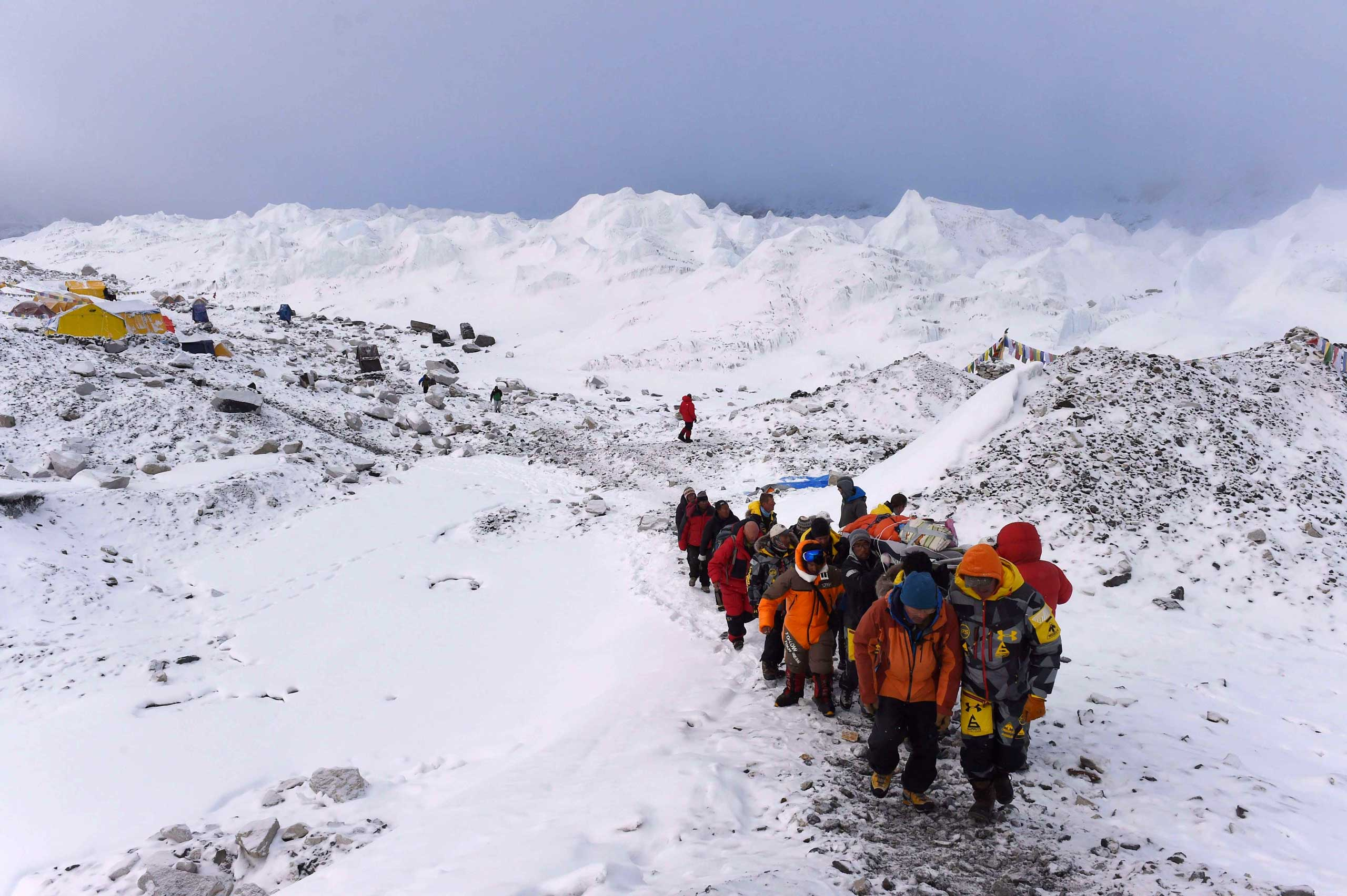 A person injured in Saturday's avalanche is carried by rescue members to be airlifted by a rescue helicopter at Everest Base Camp on April 26, 2015.