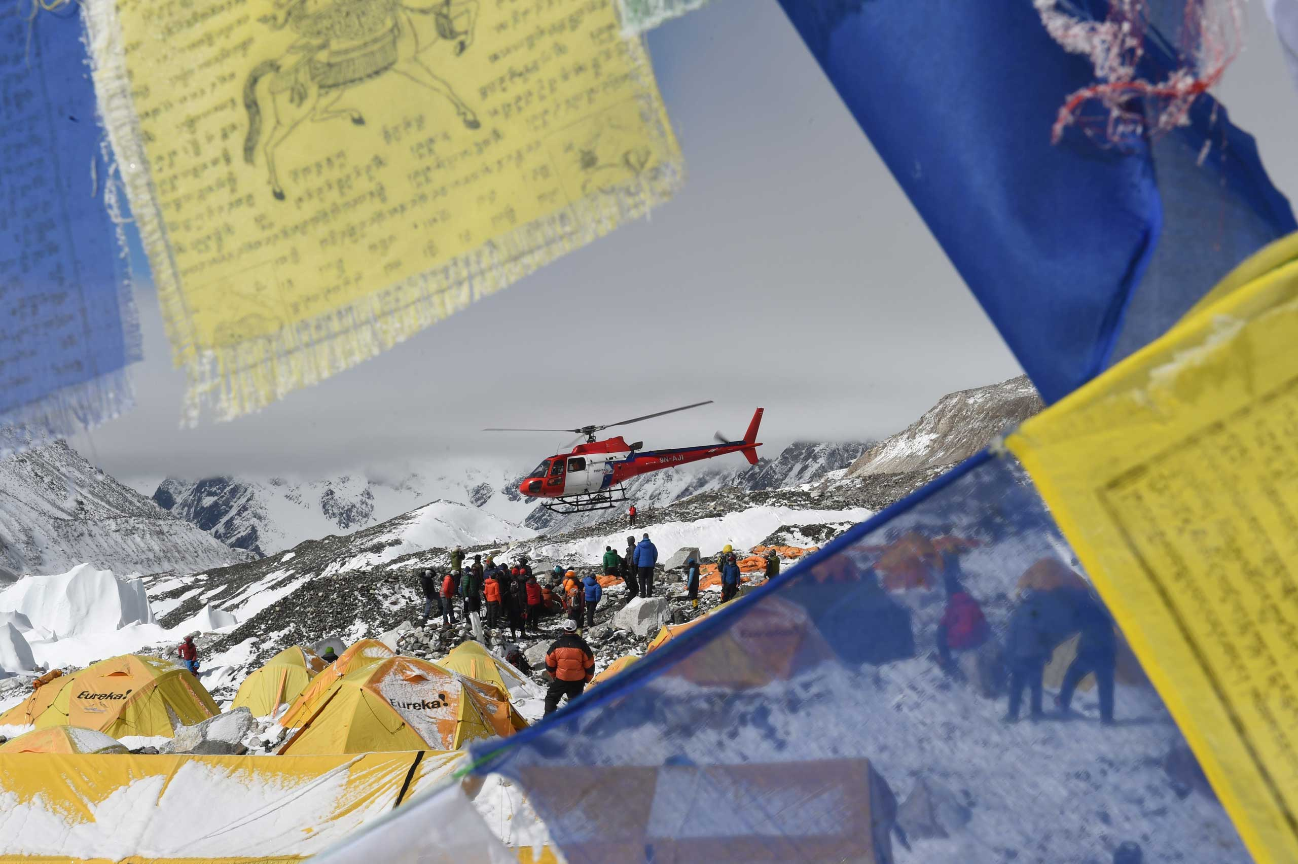 Prayer flags frame a rescue helicopter as it ferries the injured from Everest Base Camp on April 26, 2015, one day after an avalanche triggered by an earthquake outside Kathmandu, Nepal.