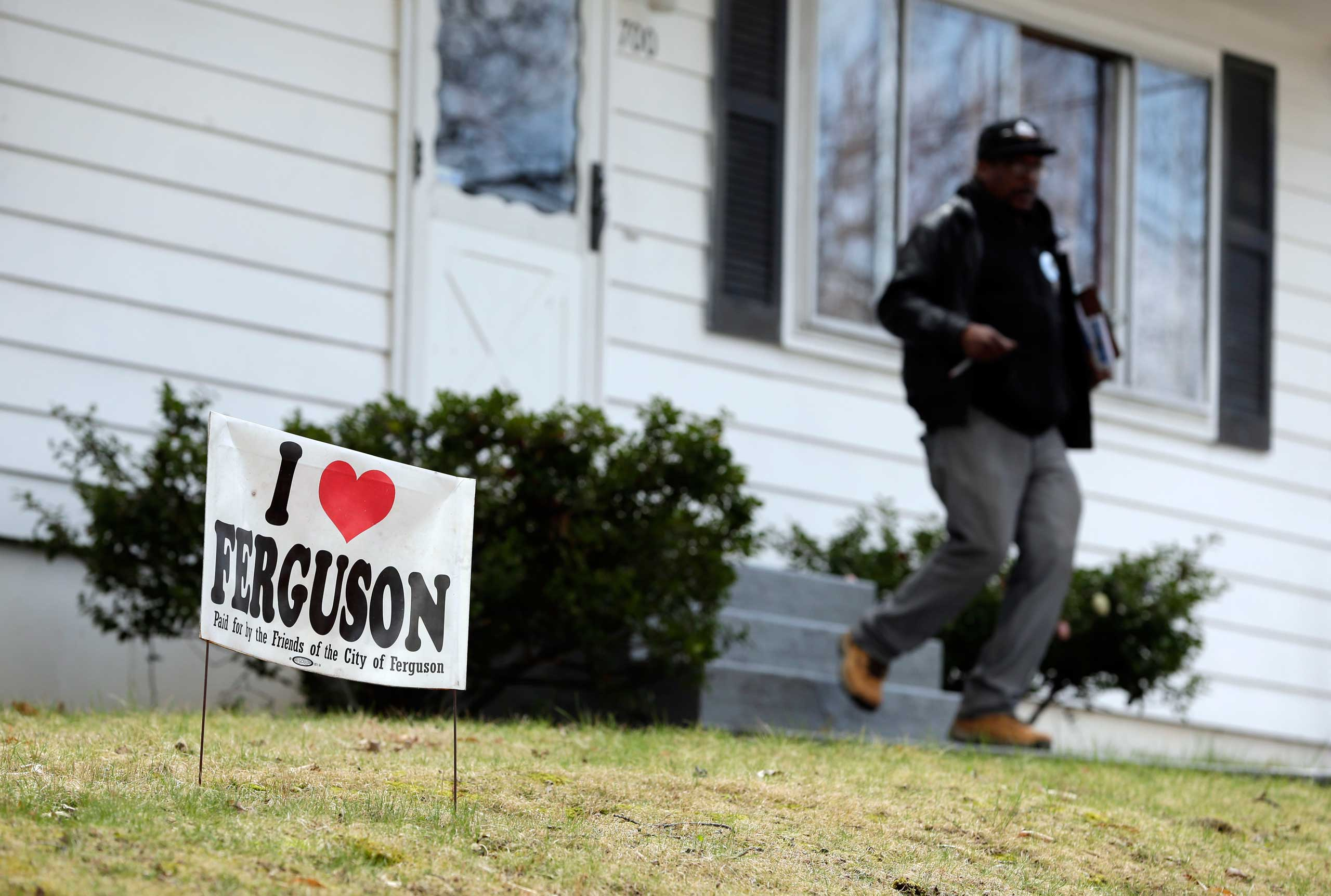 In this photo made Friday, April 3, 2015, Reginald Rounds, a volunteer with the Organization for Black Struggle, walks door-to-door while canvassing a neighborhood in Ferguson, Mo.