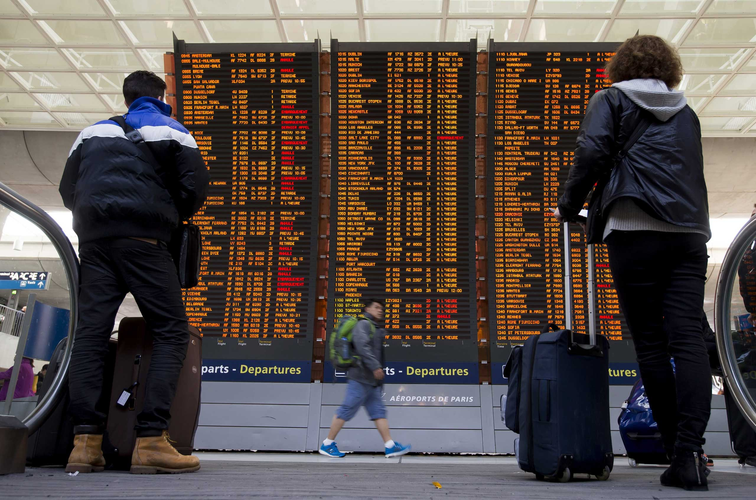 Travellers check a flight information board with various of them listed as 'cancelled' due to a strike of air traffic controllers at the Charles de Gaulle internation airport's terminal 2, in Roissy, near Paris, April 8, 2015.