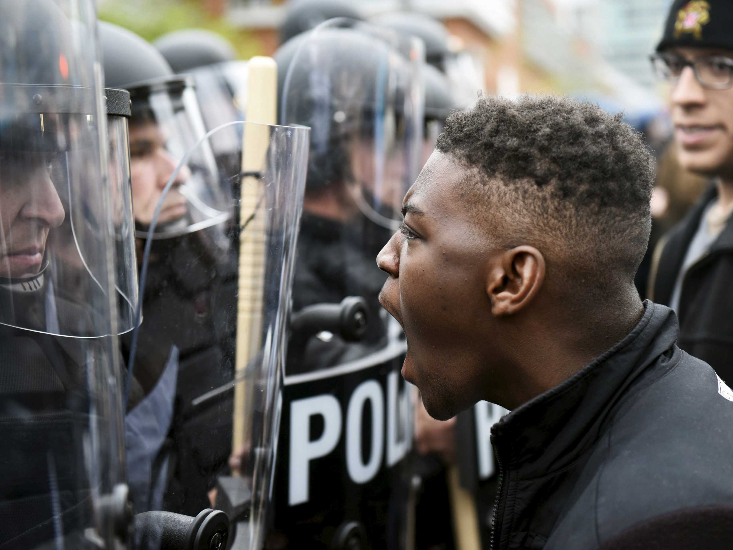 A demonstrator confronts police near Camden Yards during a protest in Baltimore on April 25, 2015.