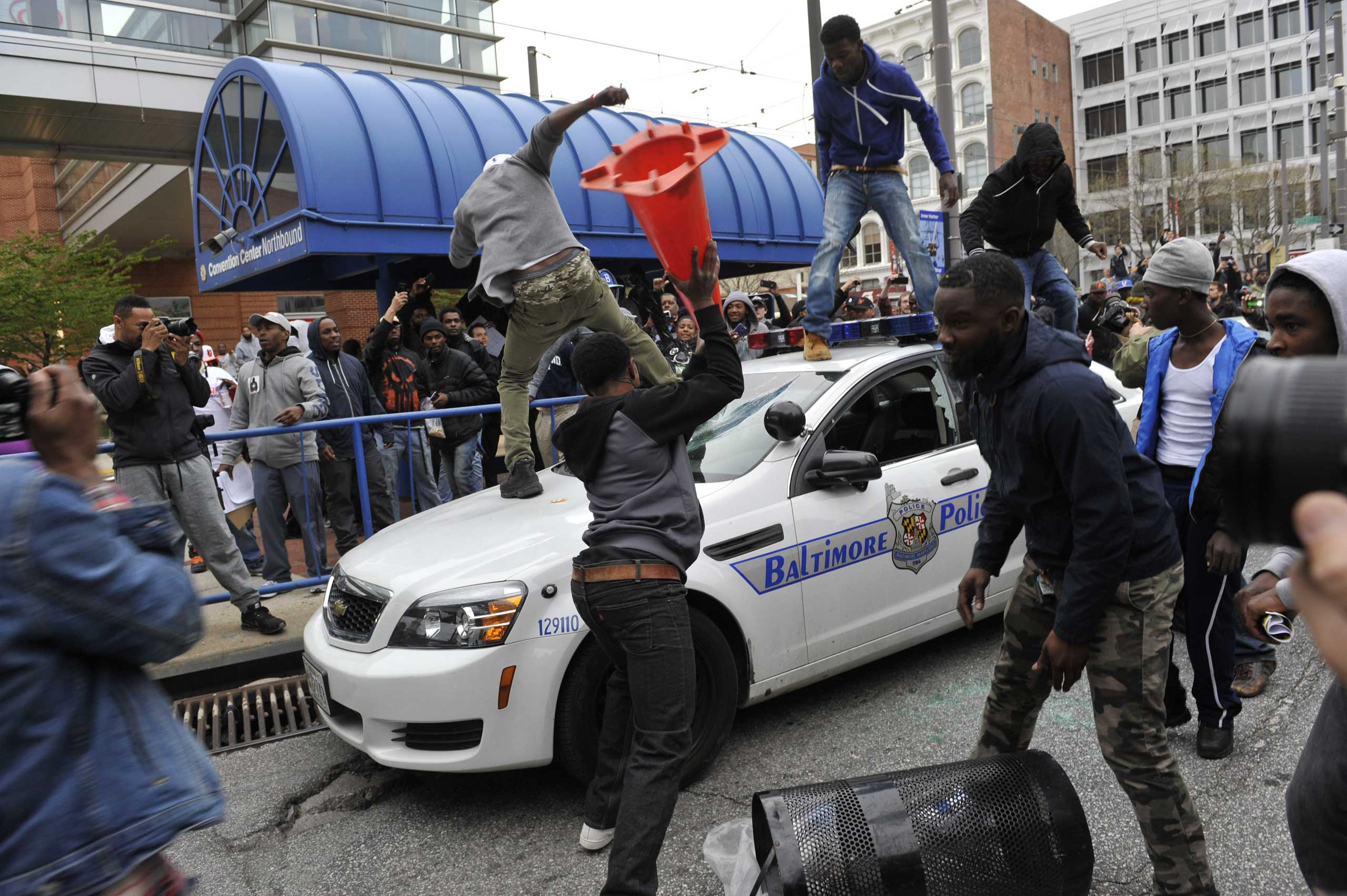 Protesters attack Baltimore police cars and suspected police cars during a demonstration against police brutality in downtown Baltimore on April 25, 2015.
