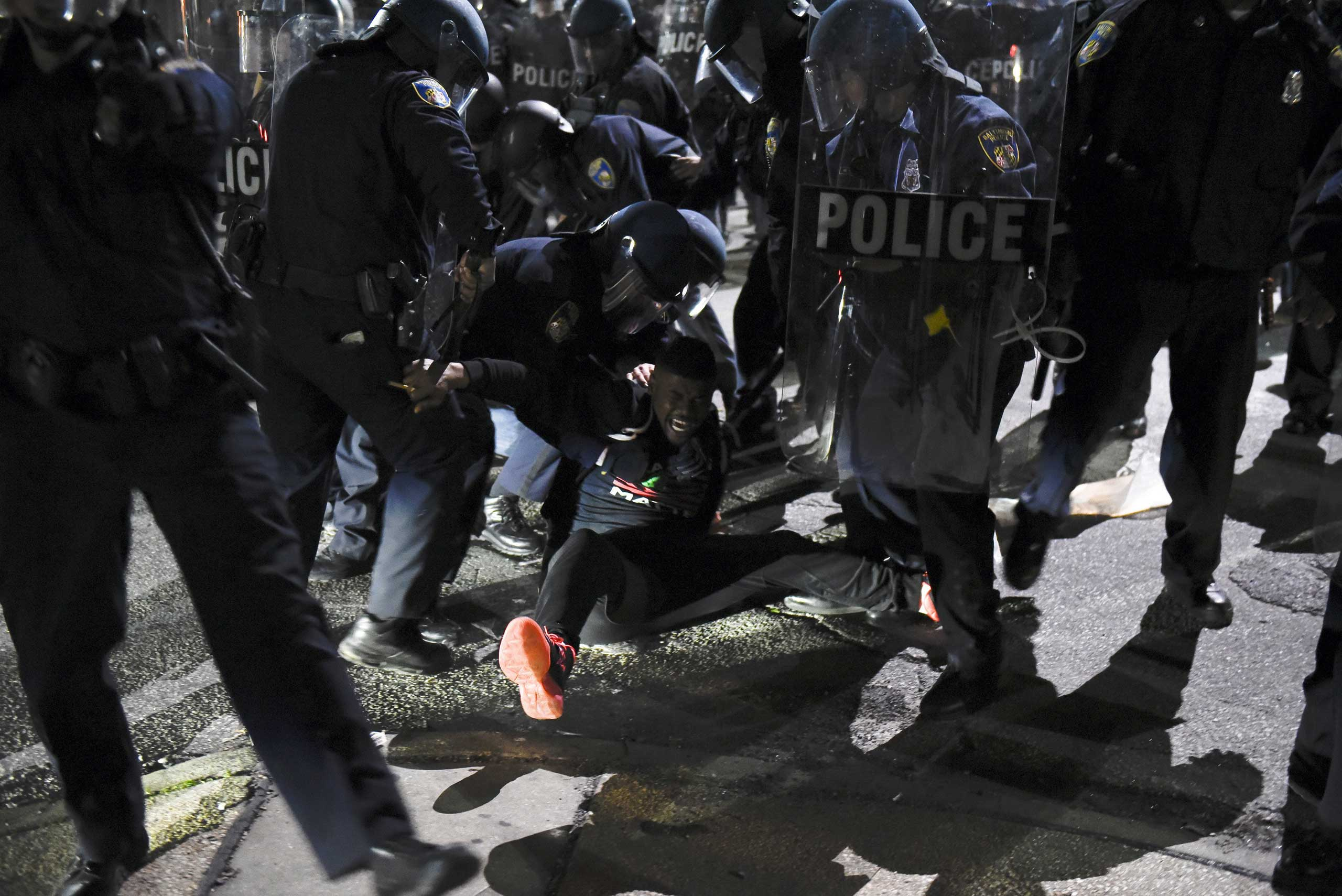 Law enforcement officers detain a demonstrator on Gilmore Avenue near Baltimore Police Department Western District during a protest against the death of Freddie Gray in police custody, in Baltimore on April 25, 2015.