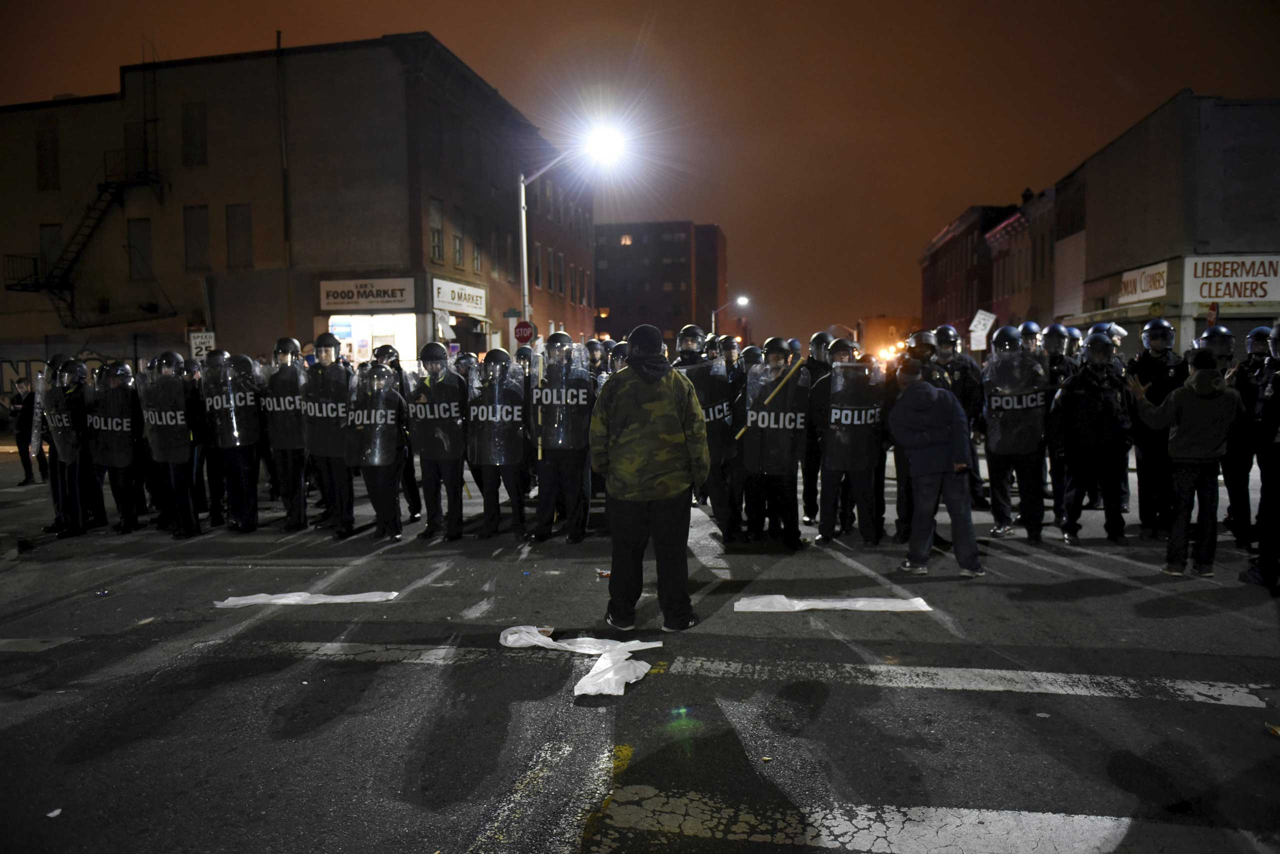 A demonstrator confronts law enforcement officers near Baltimore Police Department Western District in Baltimore on April 25, 2015.