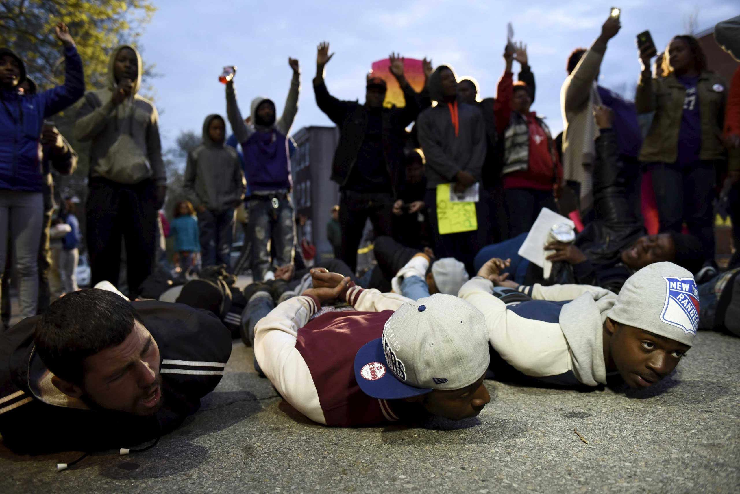 Demonstrators pretend to be arrested in front of the Baltimore Police Department Western District station to protest against the death in police custody of Freddie Gray in Baltimore on April 23, 2015.