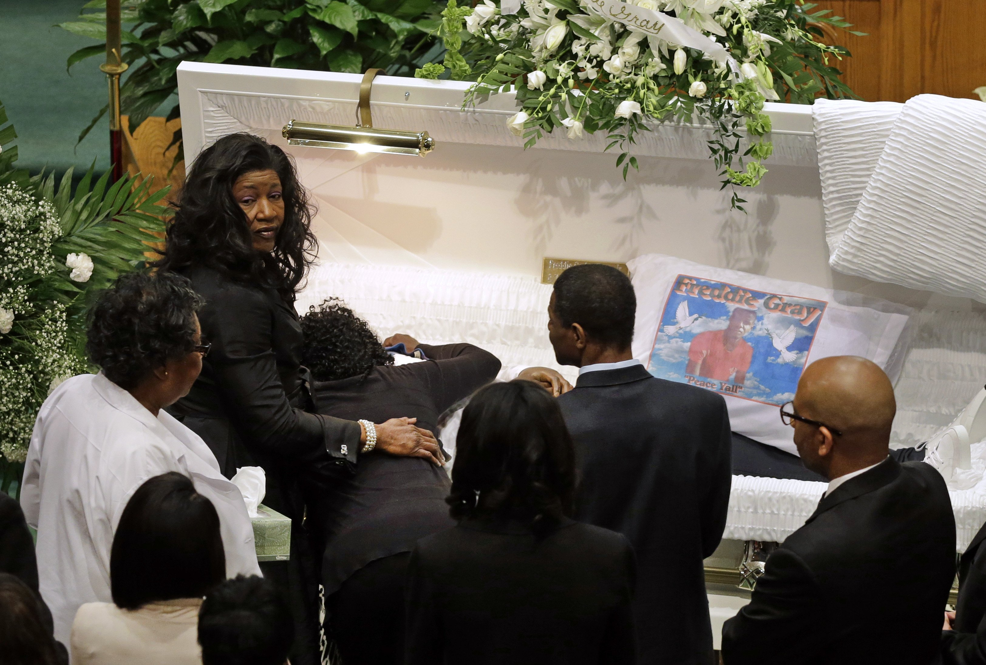 Gloria Darden, mother of Freddie Gray, is comforted as she embraces his body before his funeral at New Shiloh Baptist Church in Baltimore on April 27, 2015.