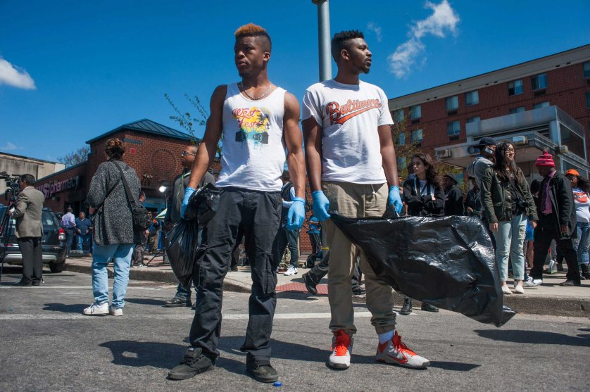 Cleanup volunteers stand in the intersection of North Avenue and Pennsylvania Avenue in the wake of riots in Baltimore on April 28, 2015.