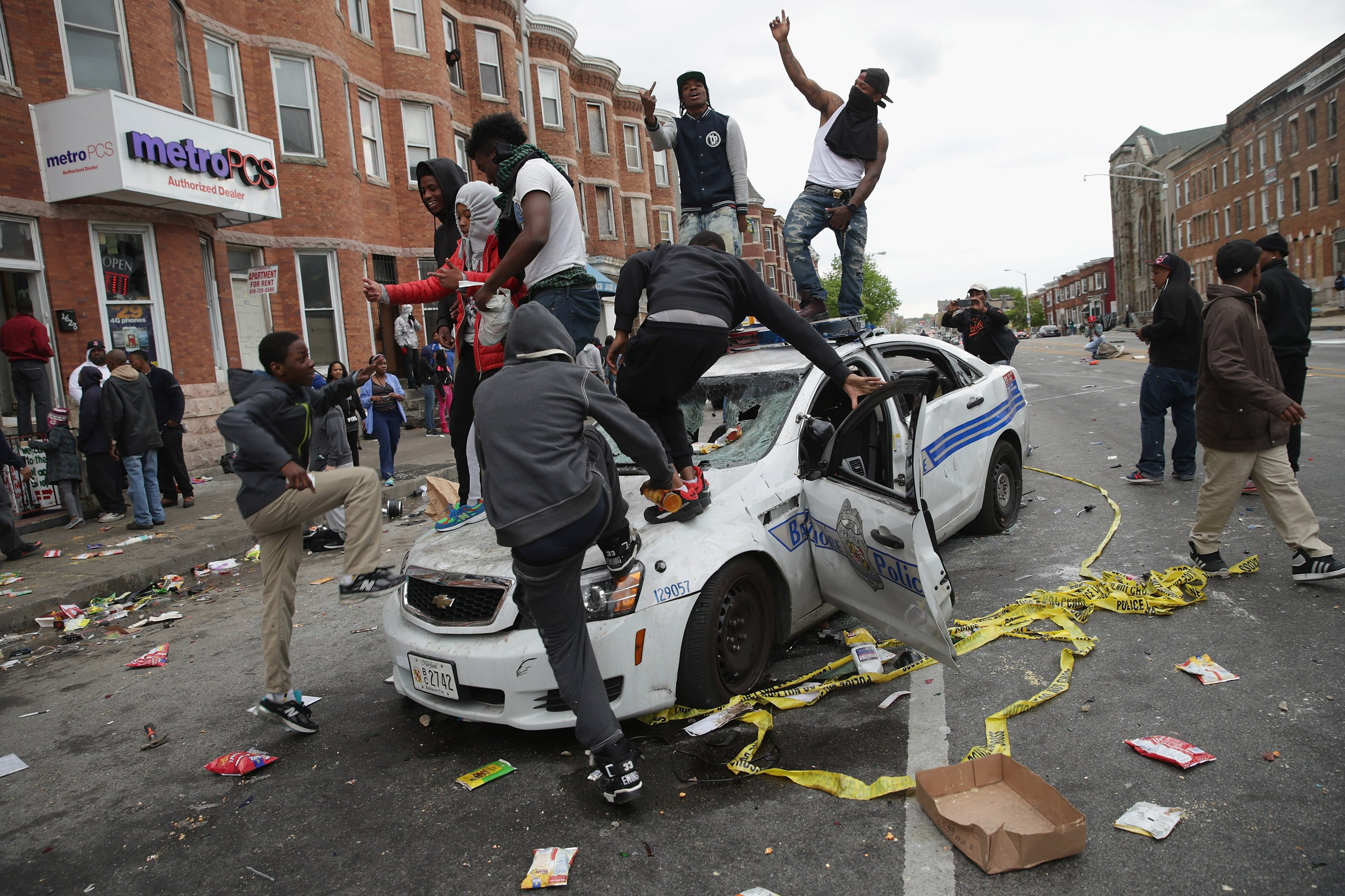 Demonstrators climb on a destroyed Baltimore Police car in the street near the corner of Pennsylvania and North avenues during violent protests following the funeral of Freddie Gray in Baltimore on April 27, 2015.
