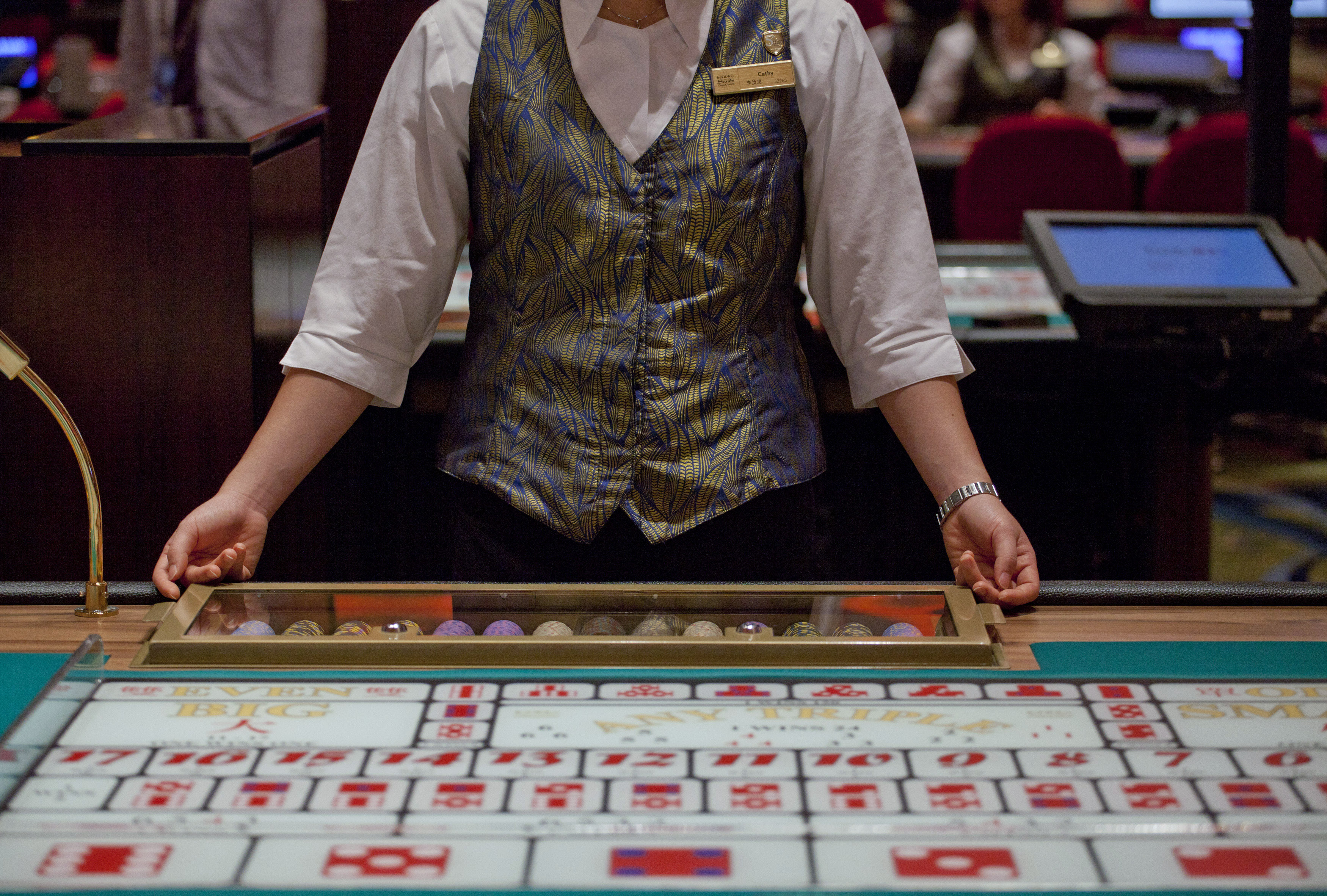 A croupier sits in front of a gaming table inside a casino on the opening day of Sheraton Macao hotel at Sands Cotai Central in Macau September 20, 2012